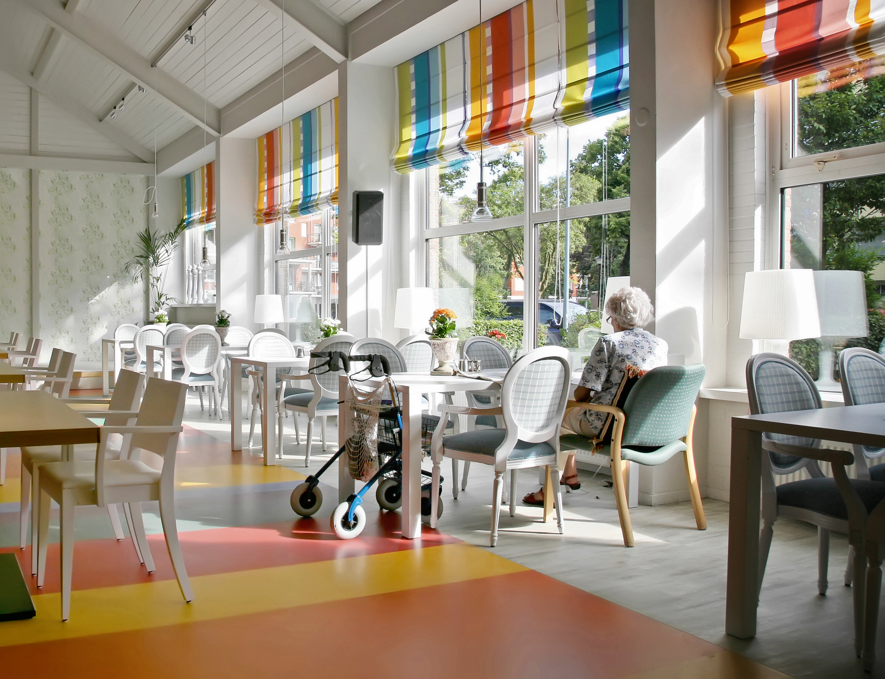An older women site alone at a table in a colorful, sunlit room. Brightly patterned curtains hang above the windows.