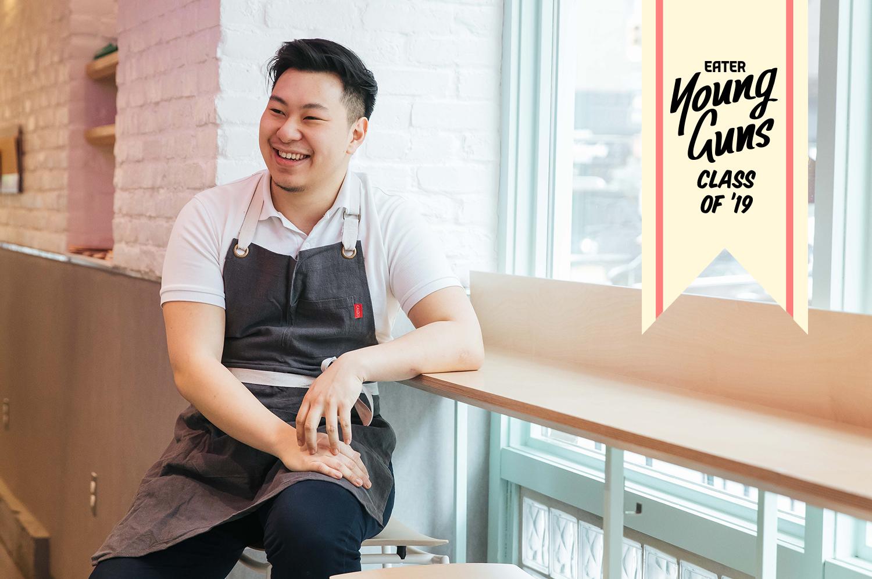 Lucas Sin sits on a stool at Junzi Kitchen.