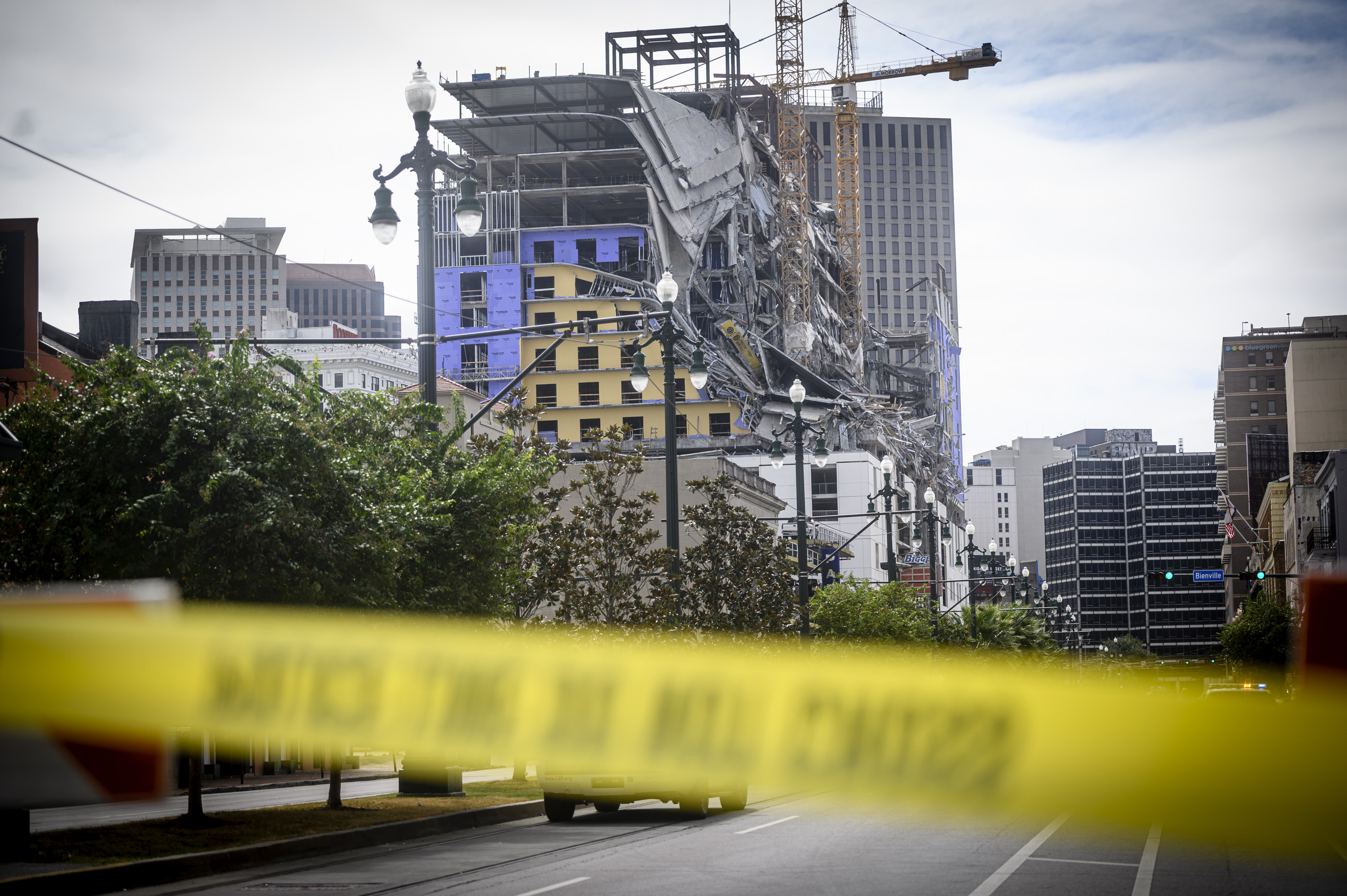 Yellow police tape with black lettering is at the foreground of a photo of a partially constructed high-rise building that has collapsed.