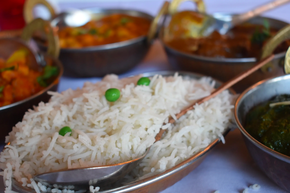 Metal bowls of basmati rice, orange curries, and more Indian food on a white table.