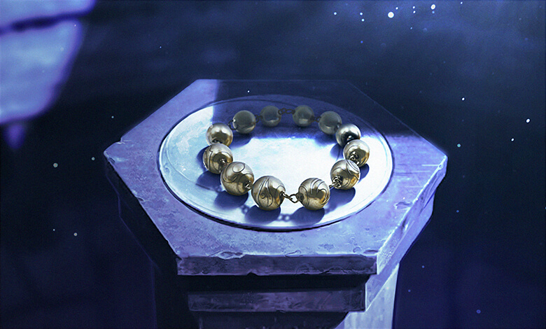 A beaded bracelet sits atop a dark pedestal