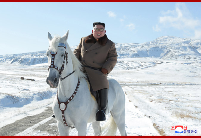 Kim on a white horse in a snowy mountain landscape.