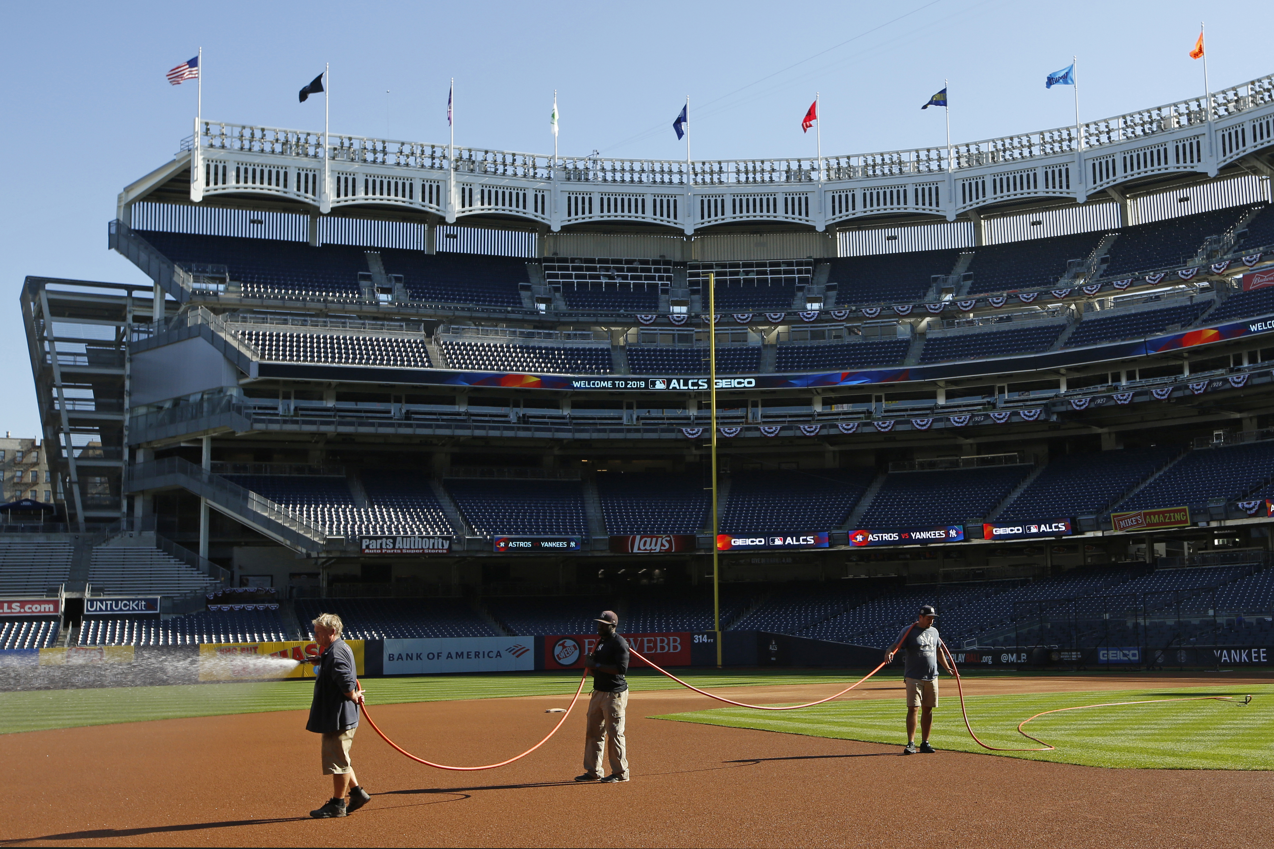 Groundskeepers water the field at Yankee Stadium, Monday, Oct. 14, 2019, in New York, in perparation for Game 3 in the American League Championship Series between the New York Yankees and the Houston Astros. (AP Photo/Kathy Willens) ORG XMIT: OTKKW104