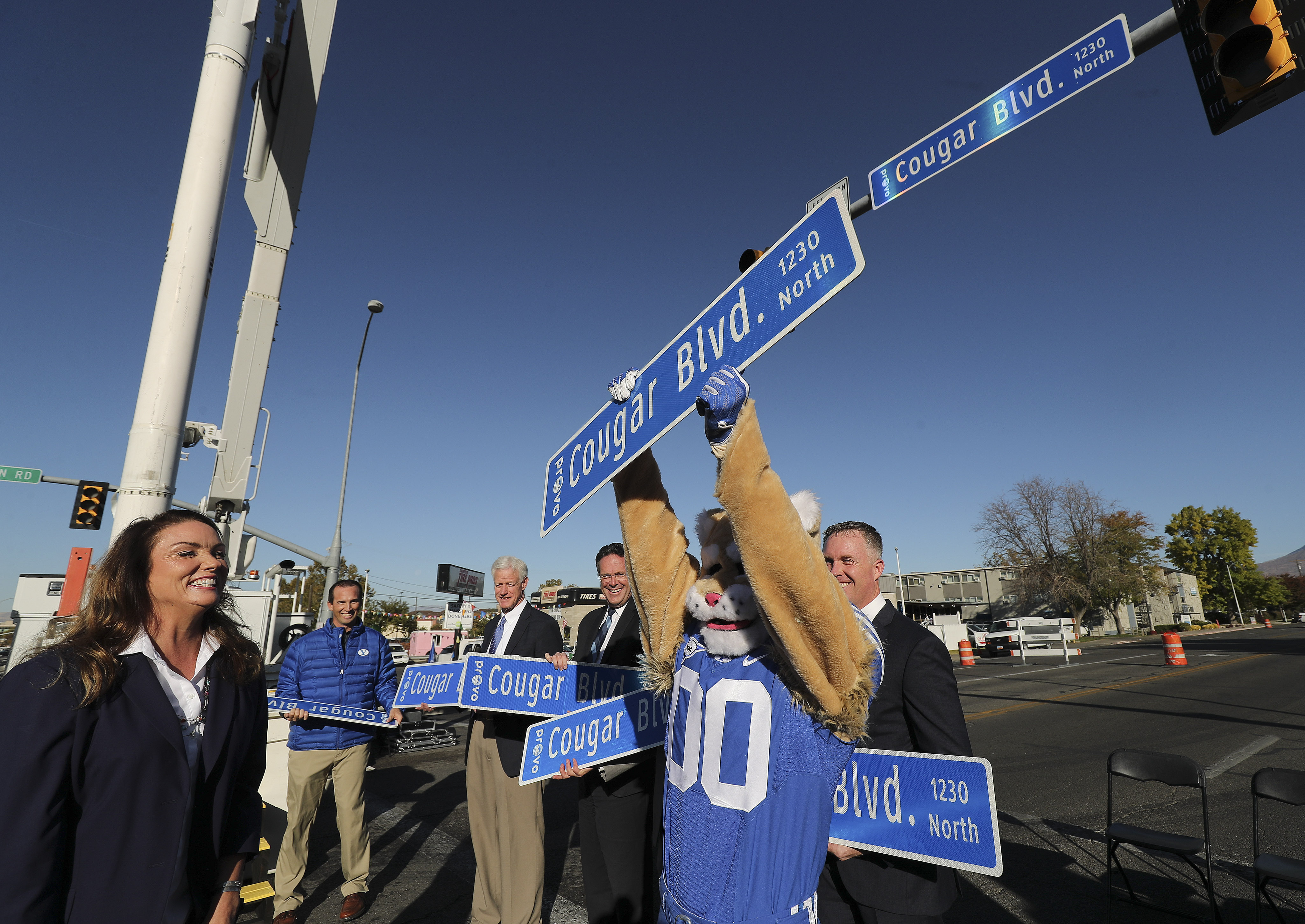Provo Mayor Michelle Kaufusi, left, Cosmo, Brigham Young University's mascot, and others celebrate the unveiling of Cougar Boulevard during a ceremony in Provo on Wednesday, Oct. 16, 2019. The road, which used to be Bulldog Boulevard (1230 North), was renamed to mark the 144th anniversary of the founding of the university, which is celebrating homecoming this week.