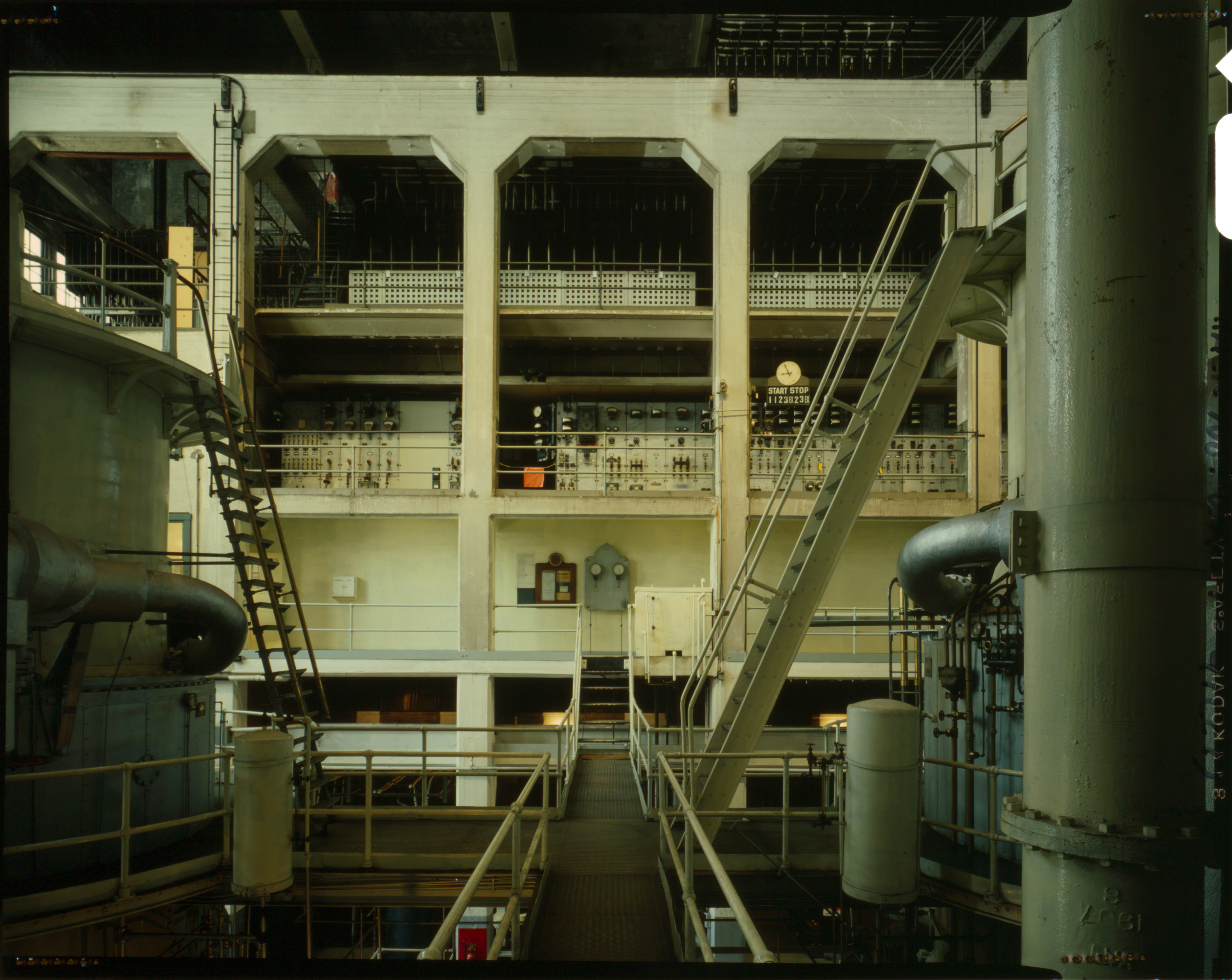 The interior of an industrial facility. Four concrete arches contain three floors of open railings.