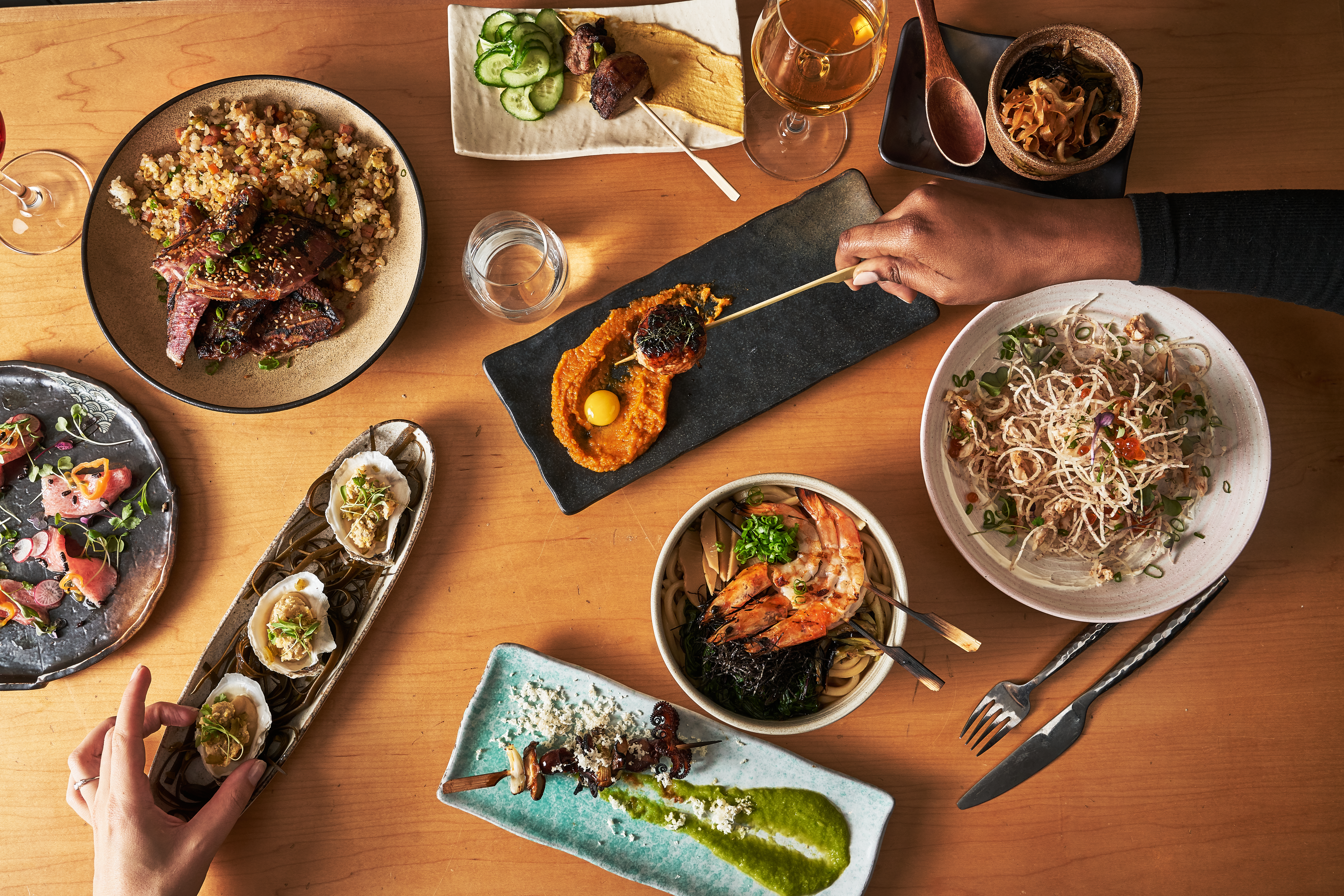 An aerial view of a spread of small plates topped with Asian-inspired fare over a wooden table