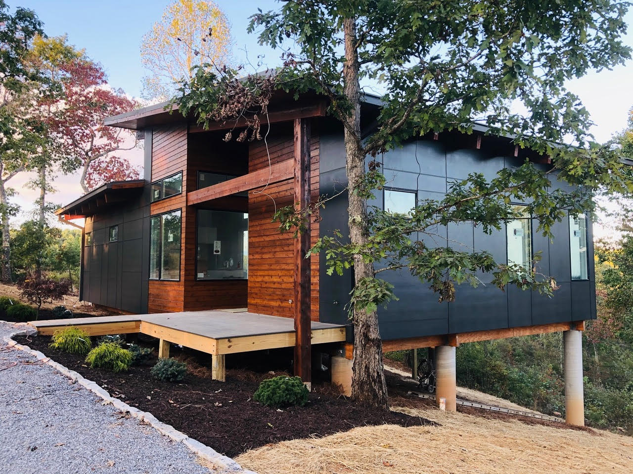 A small modern home on a hill surrounded by woods.