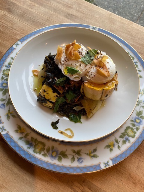 A close up of a poached egg dish, on top of squash, kale, and tomatoes.