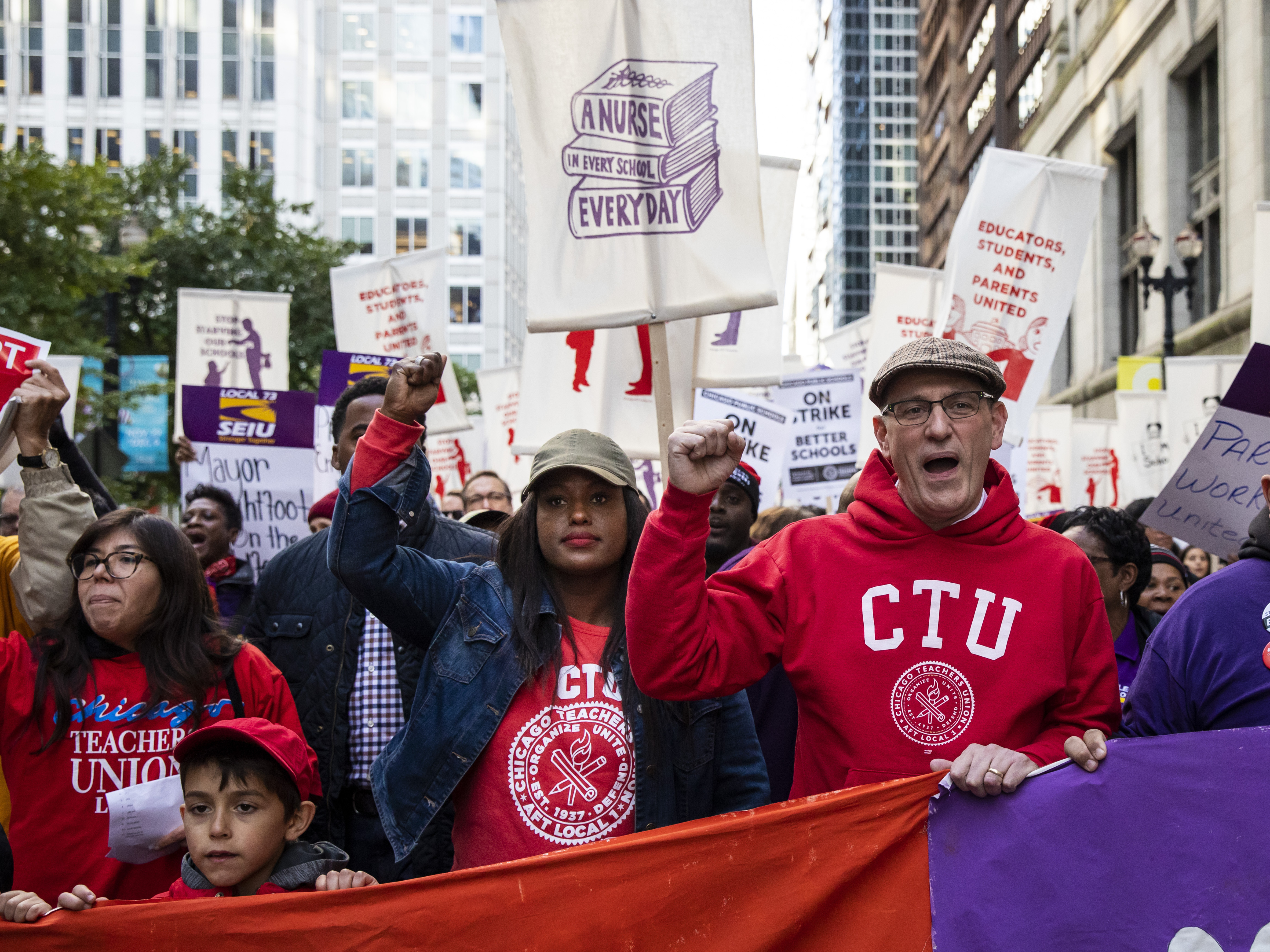 Chicago Teachers Union President Jesse Sharkey, center right, and Vice President Stacy Davis Gates, center left, march with members of the CTU and SEIU Local 73 through the Loop on Monday.