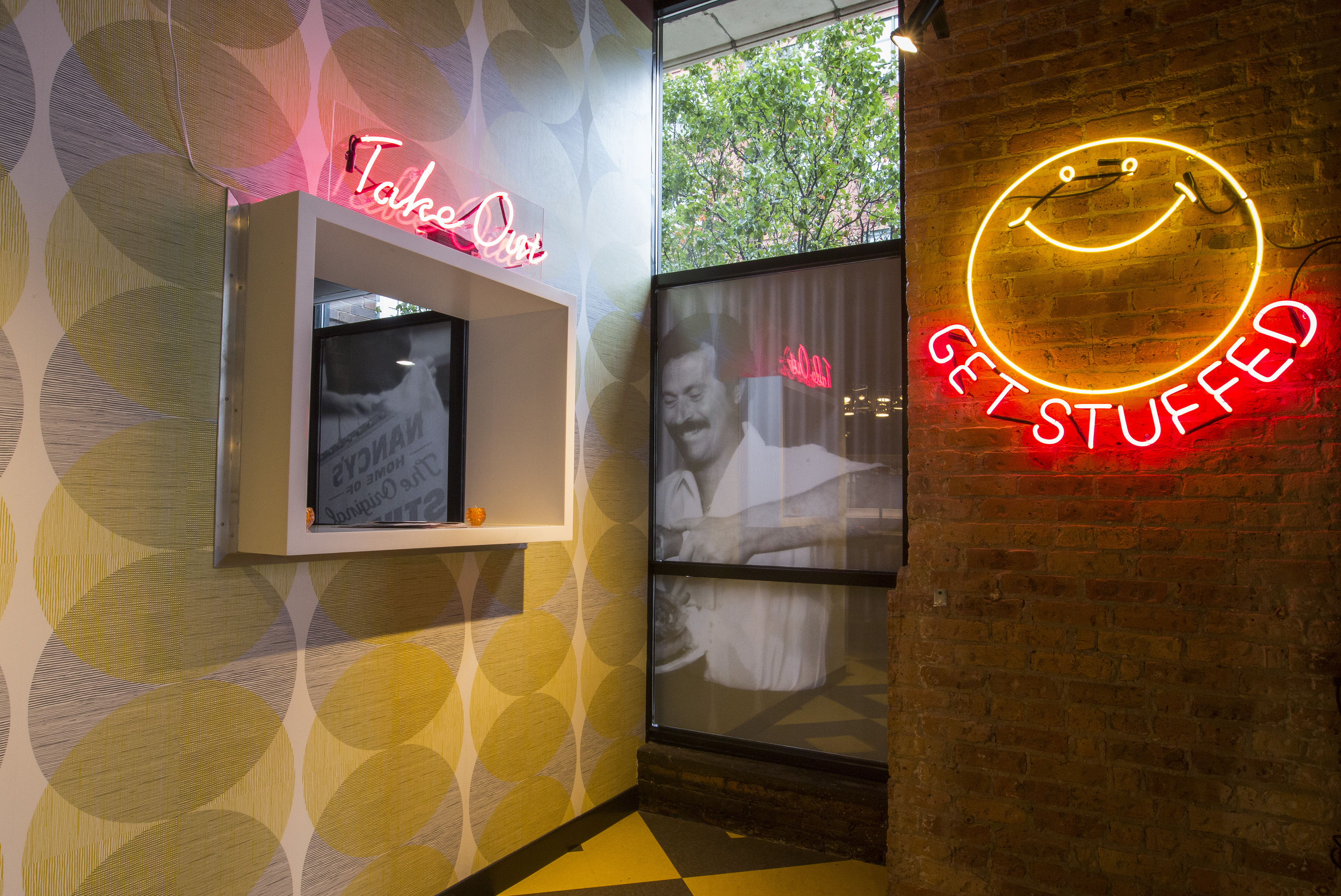 """A neon sign with a happy face and the words """"Get stuffed"""" on a wall near a take-out window."""