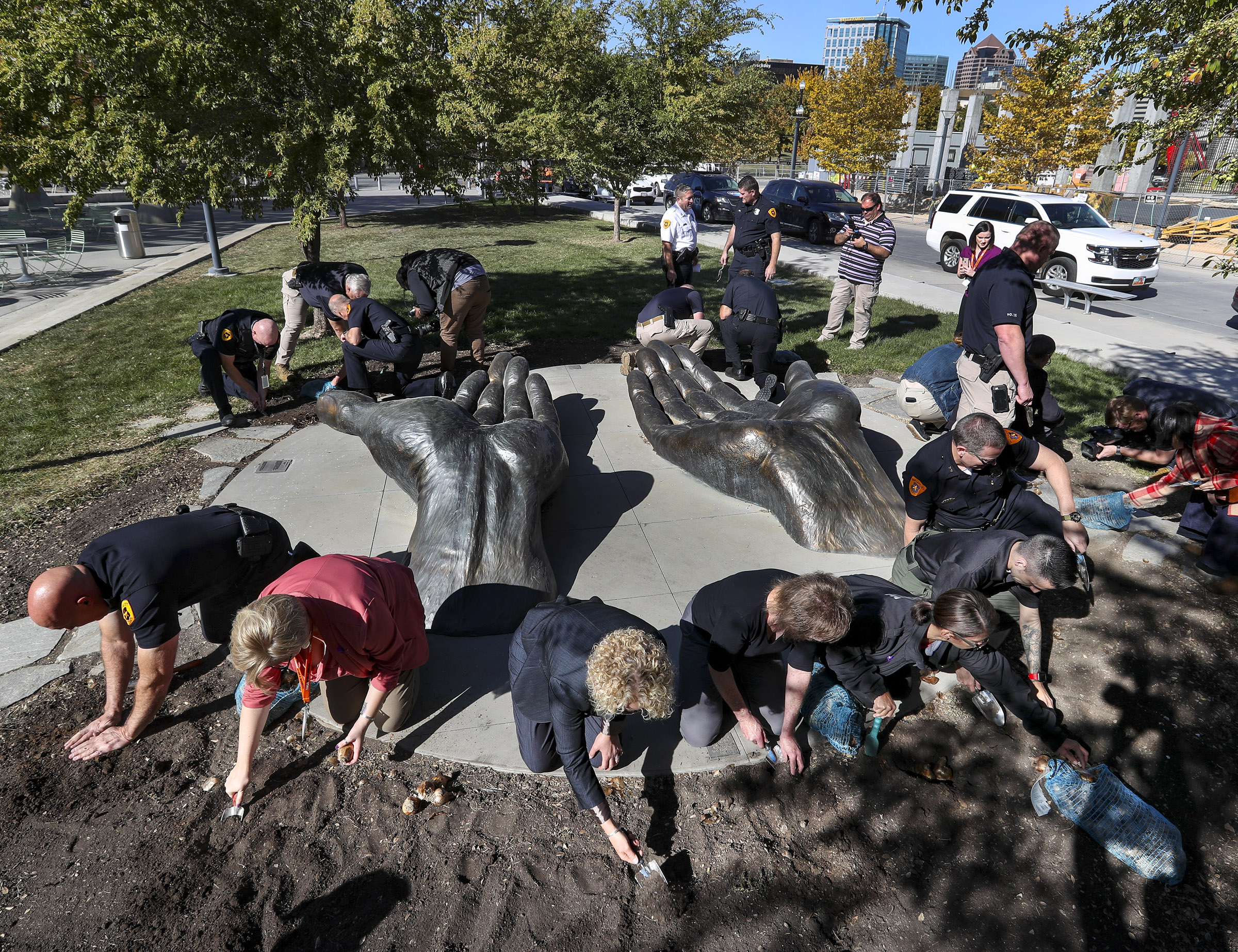 Salt Lake City Police Chief Mike Brown, bottom left, Amy Fladmo, director of the YWCA Women in Jeopardy Crisis Shelter, Salt Lake City Mayor Jackie Biskupski and others plant daffodil bulbs outside the Public Safety Building in Salt Lake City on Wednesday, Oct. 16, 2019, in honor of those who lost their lives to domestic violence in Utah last year.