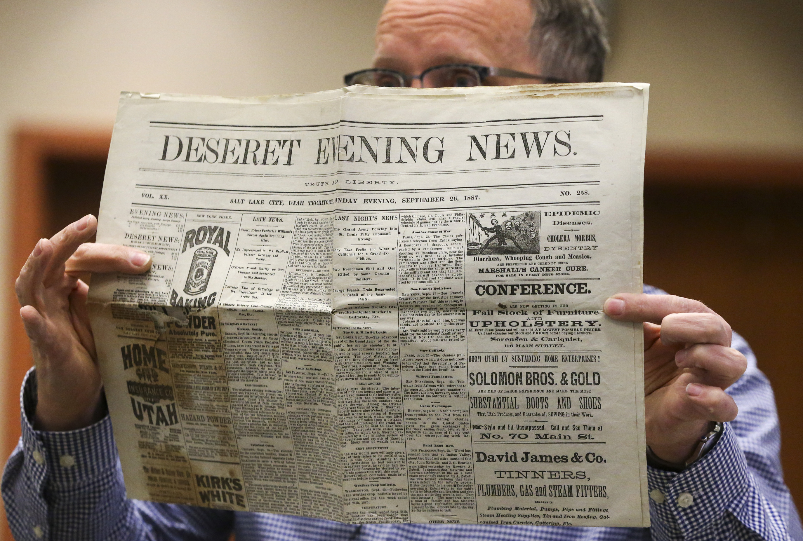 Alan Barnett, a local government archivist with the Utah Division of Archives and Records Service, displays a copy of the Deseret Evening News as he unboxes an 1887 time capsule at the division's office in Salt Lake City on Wednesday, Oct. 16, 2019. The time capsule was discovered in the cornerstone of the Ogden Central Junior High School when it was torn down in the early 1960s. At the time, the metal box was cut open to reveal its contents, which were then returned to the box and put in storage at the Ogden School District offices. The time capsule and its contents were eventually sent to the Utah State Archives and Record Services for permanent preservation. The time capsule was reopened in celebration of American Archives Month.