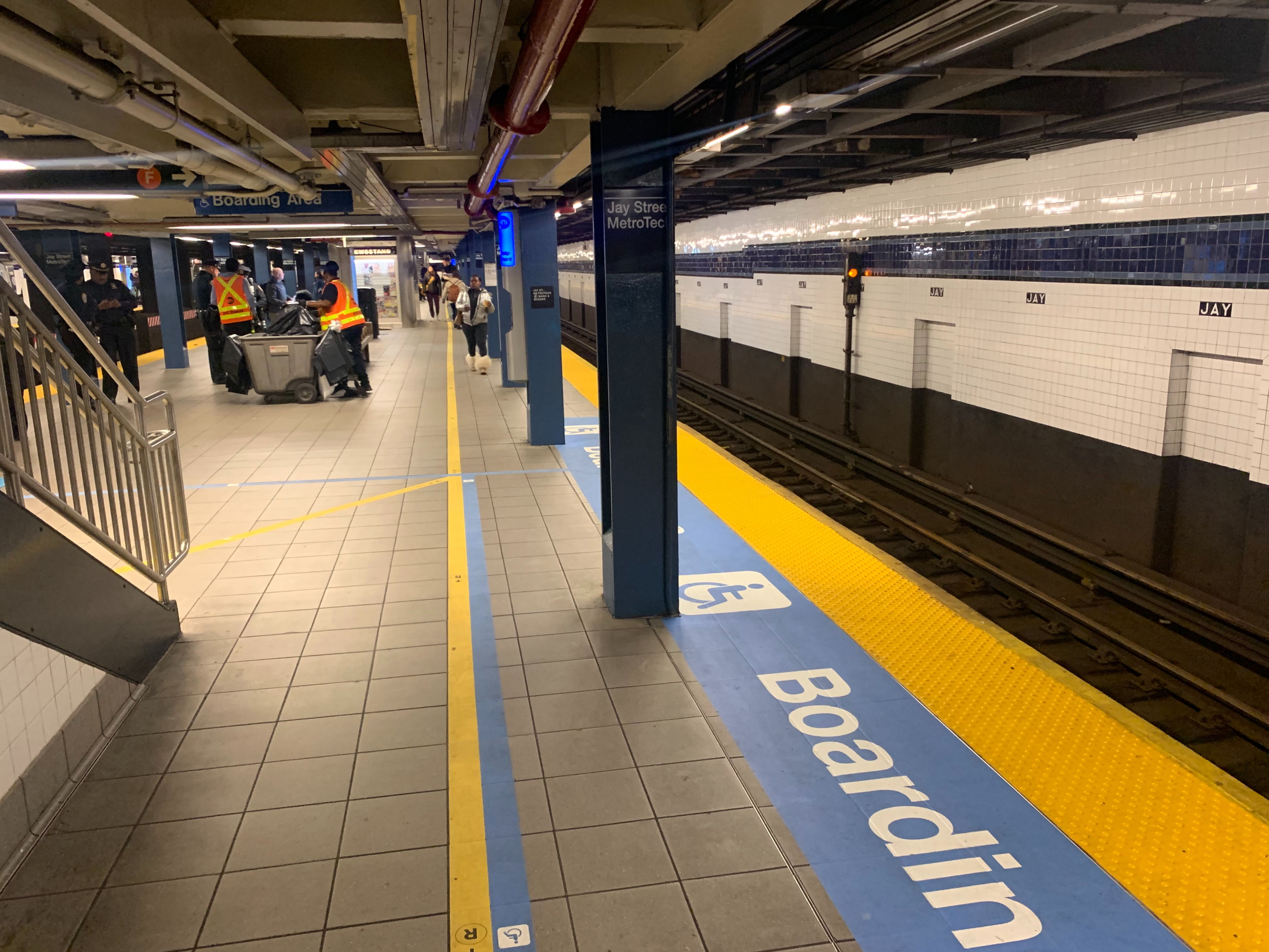 """Blue signage on the floor of the Jay Street-Metro Tech station states, """"Boarding"""" beside yellow tactile guides designed to help visually impaired passengers onto trains at the edge of the subway platform."""
