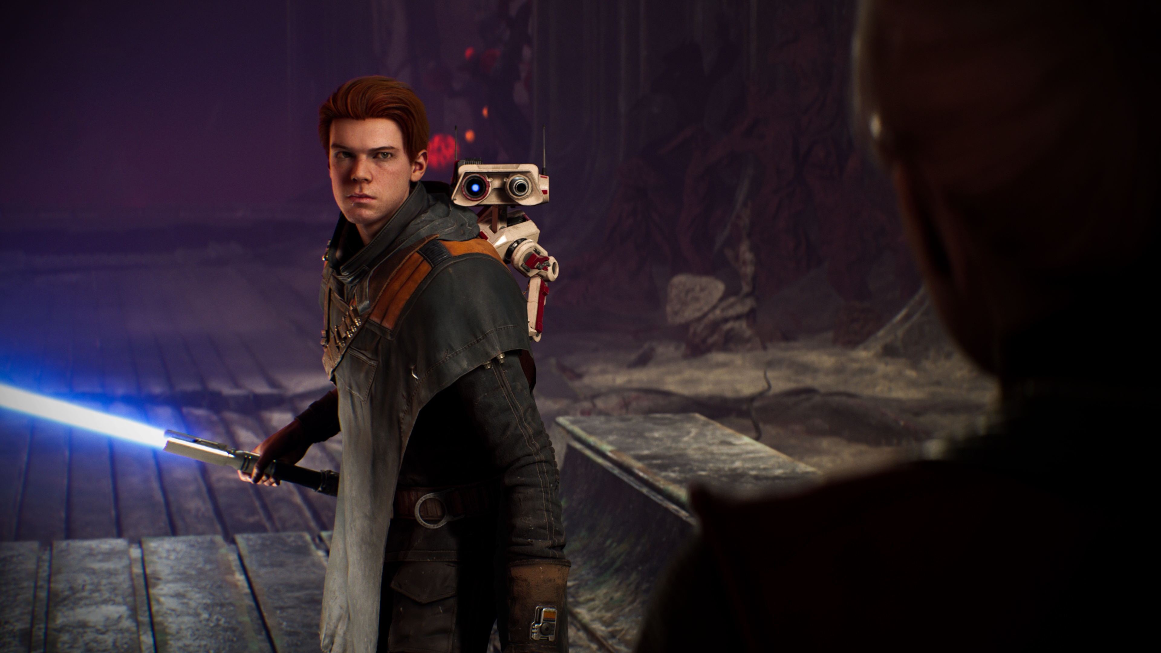 a young brown-haired man, Cal Kestis, holds a blue lightsaber in a screenshot from Star Wars Jedi: Fallen Order