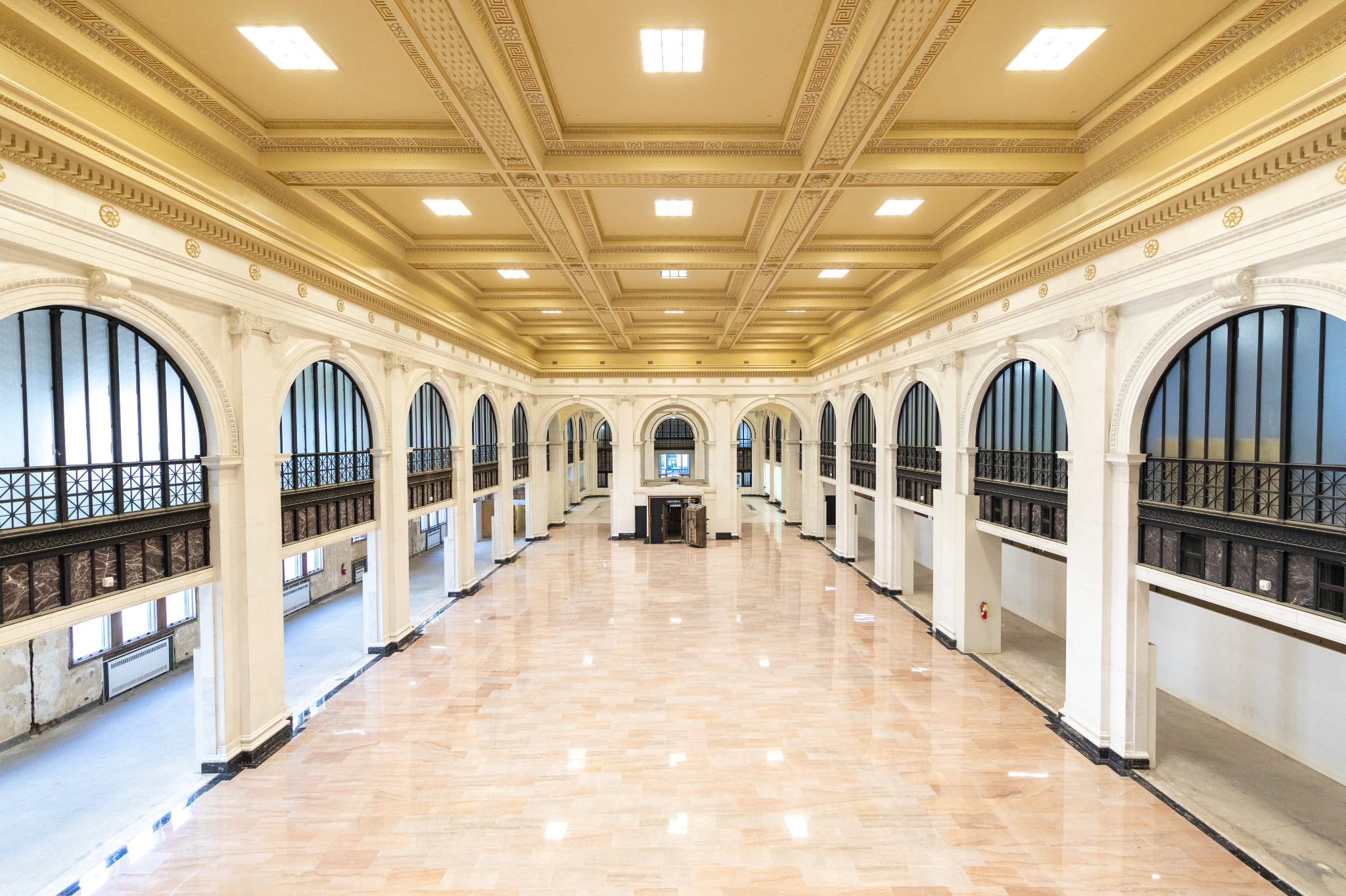 A long room with multiple arches on either side and a bank vault in the middle. There's a gold coffered ceiling.