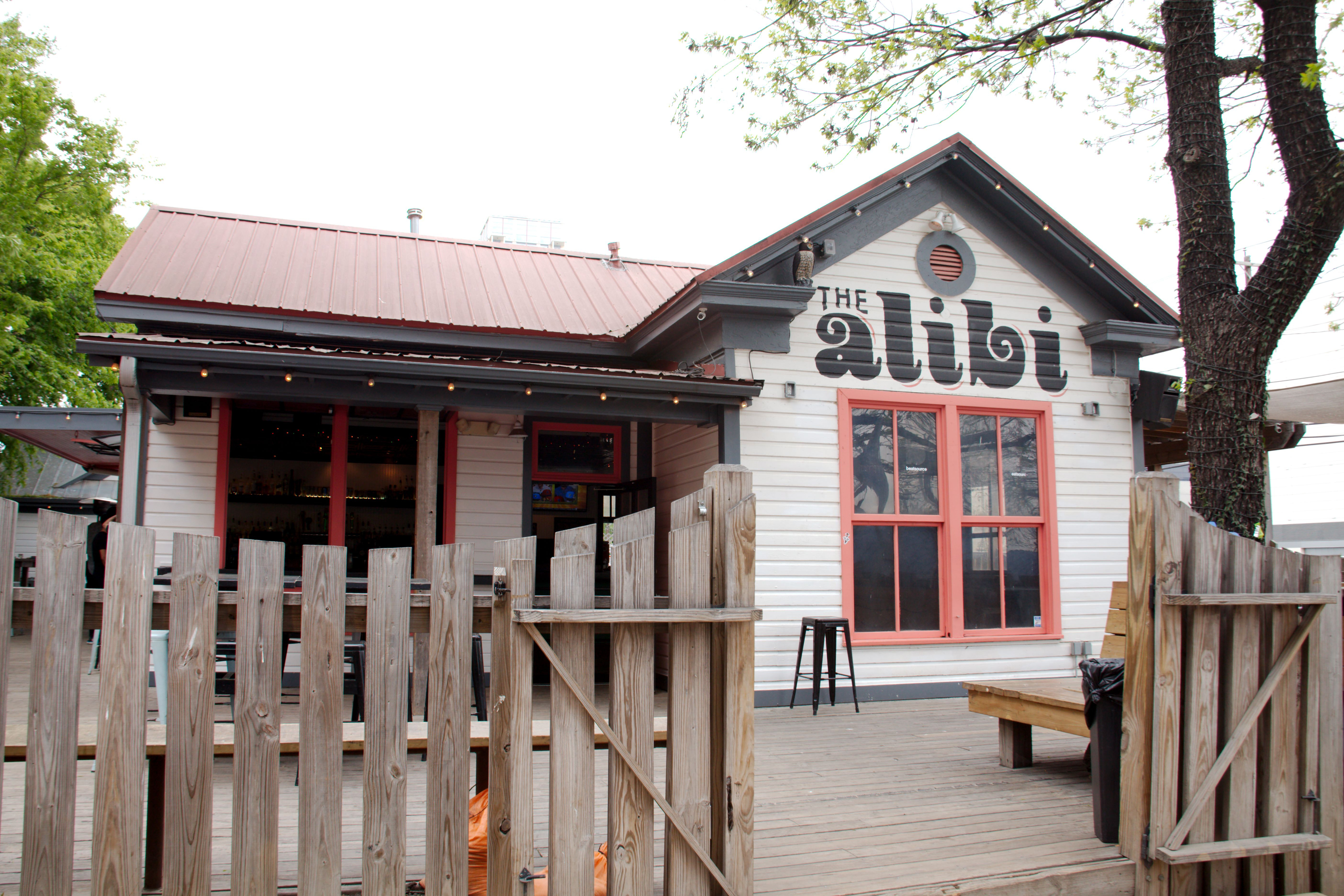 """A one-story wood-frame bungalow with an unpainted picket fence in front. A logo reading """"alibi"""" is painted on the front."""