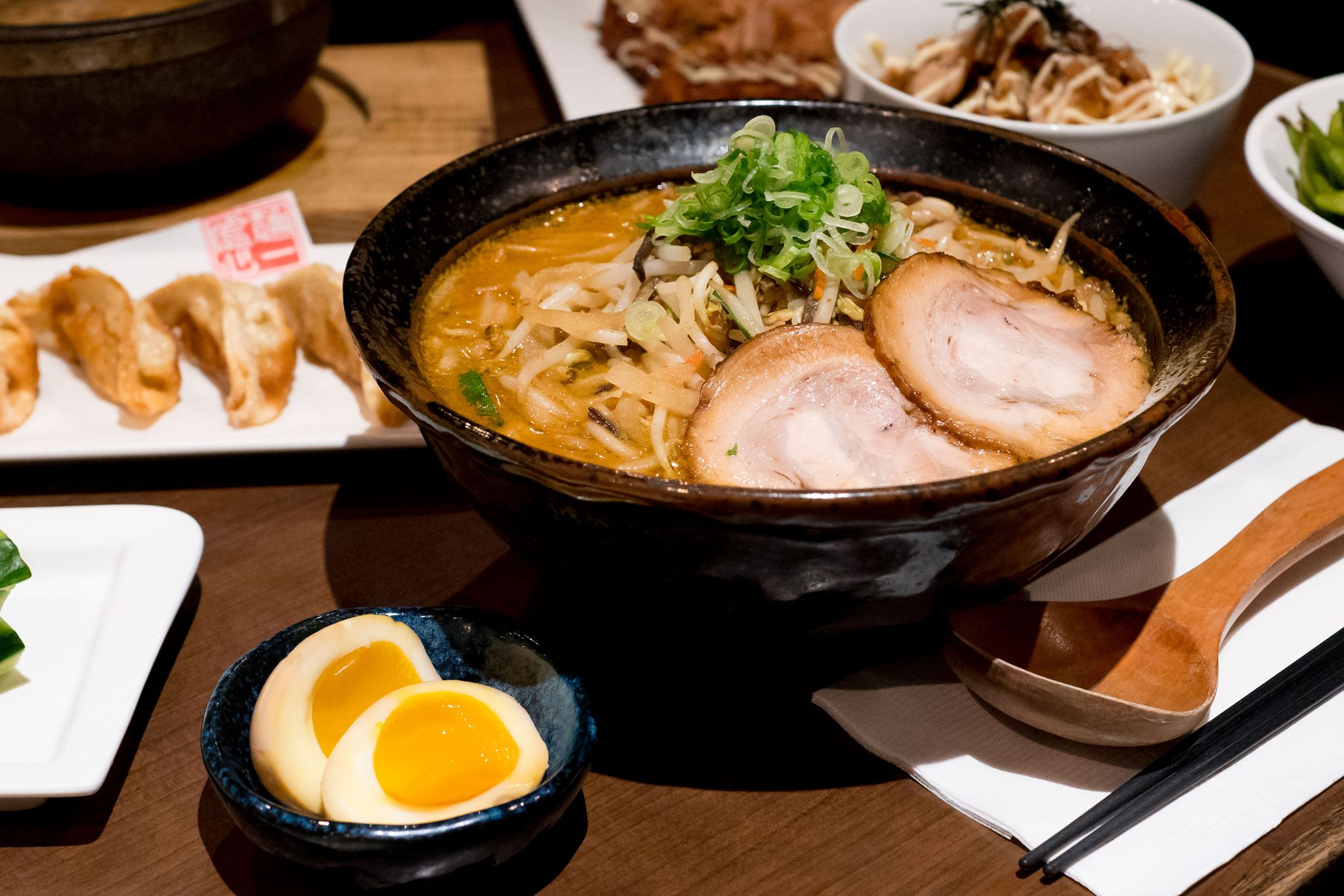 A bowl of ramen with soft-boiled egg halves in a bowl on the side.