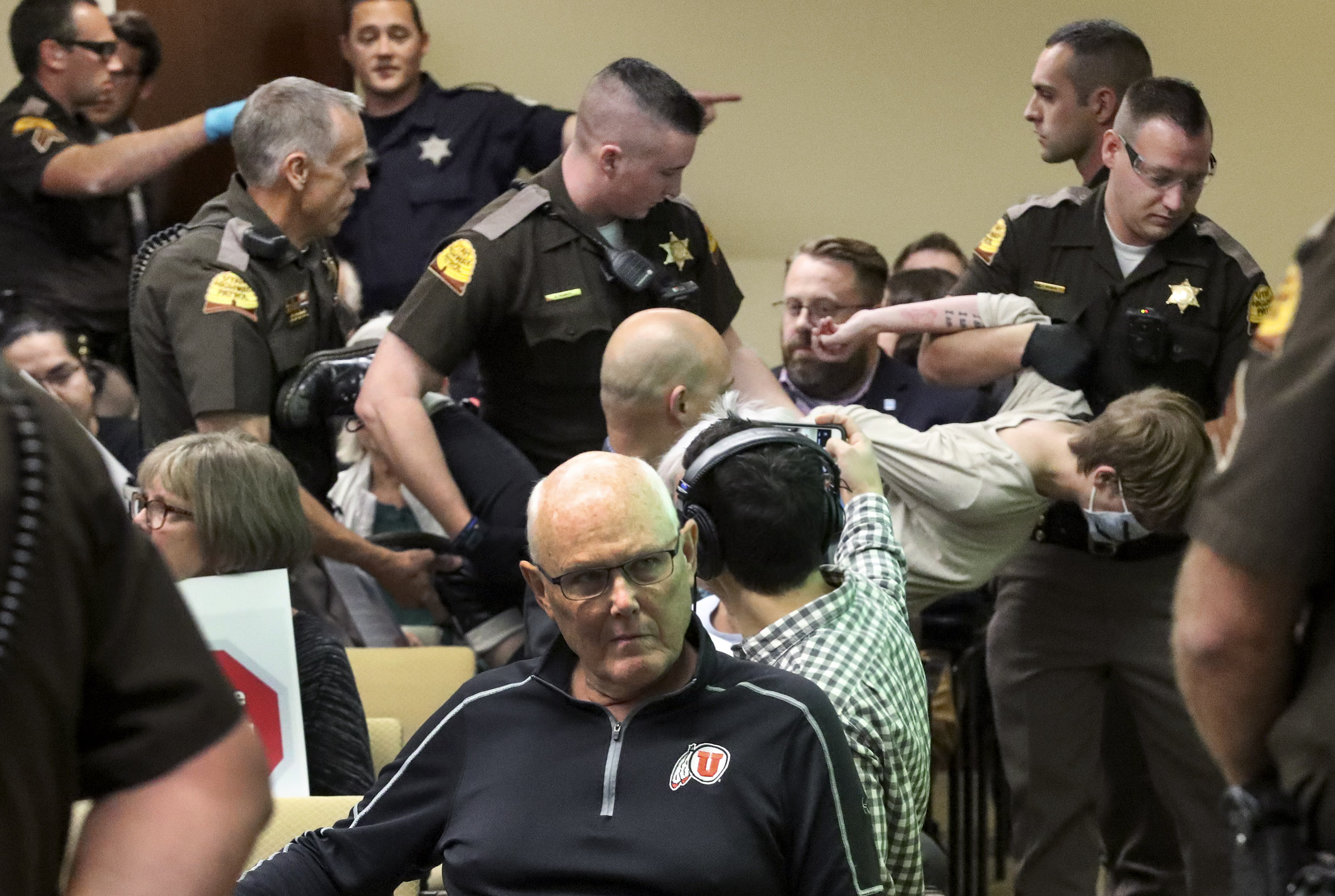 Utah Highway Patrol troopers remove a woman who was blowing a whistle through a surgical mask and disrupting the Utah Inland Port Authority Board meeting at the Capitol in Salt Lake City on Thursday, Oct. 17, 2019.