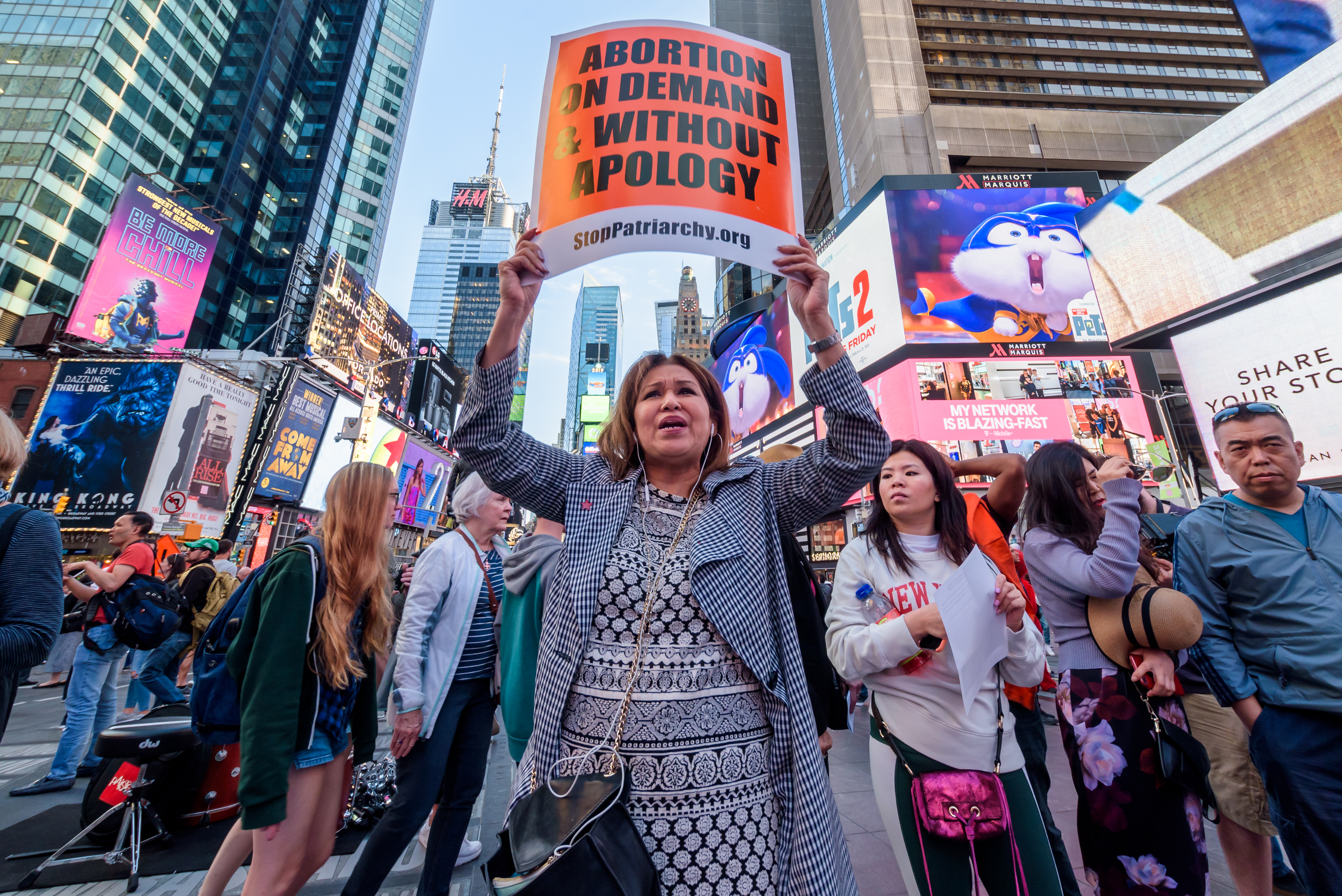 "A protester holding a sign reading ""Abortion on demand & without apology"" surrounded by other people in New York's Times Square."