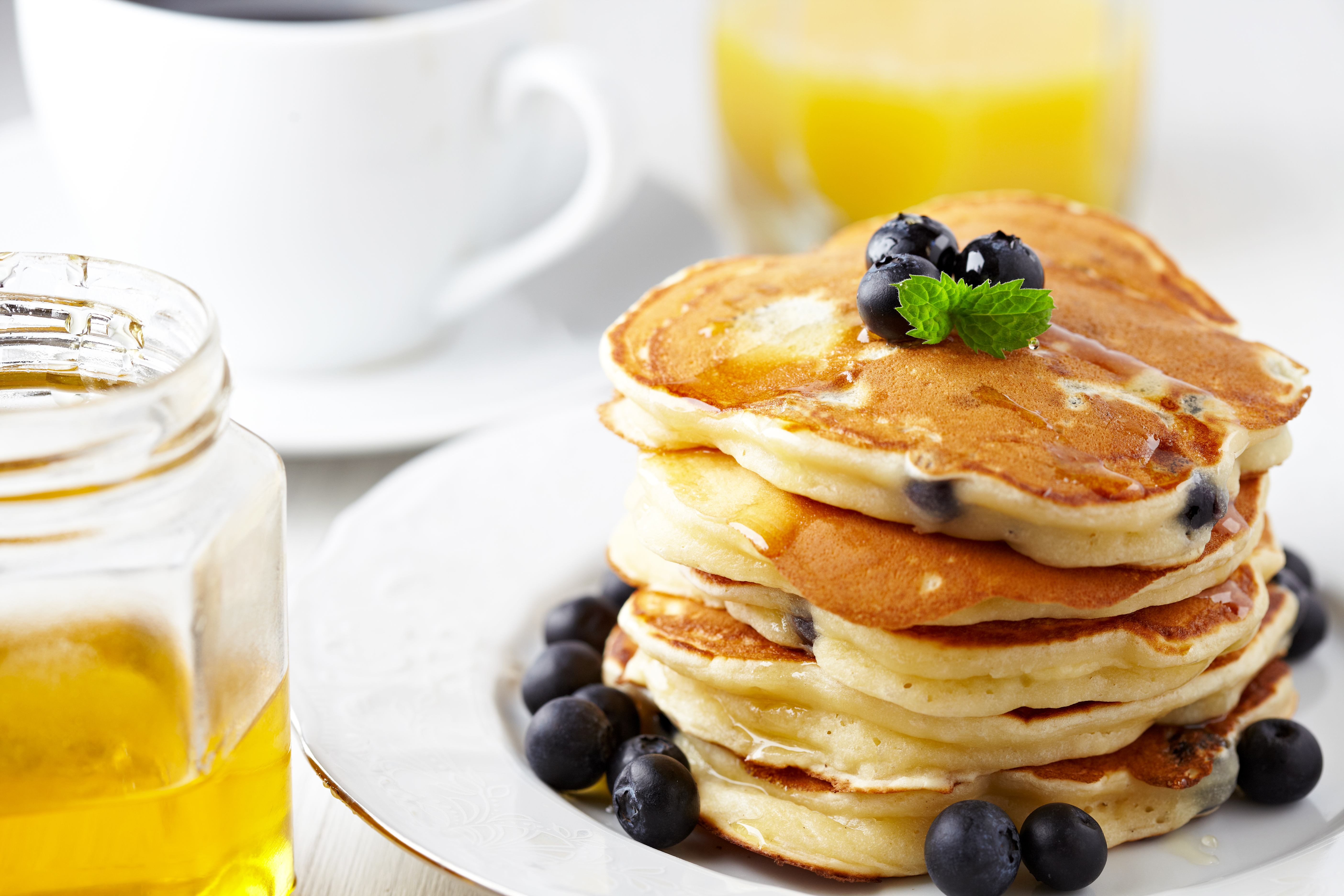 Coffee, orange juice, and a stack of blueberry pancakes
