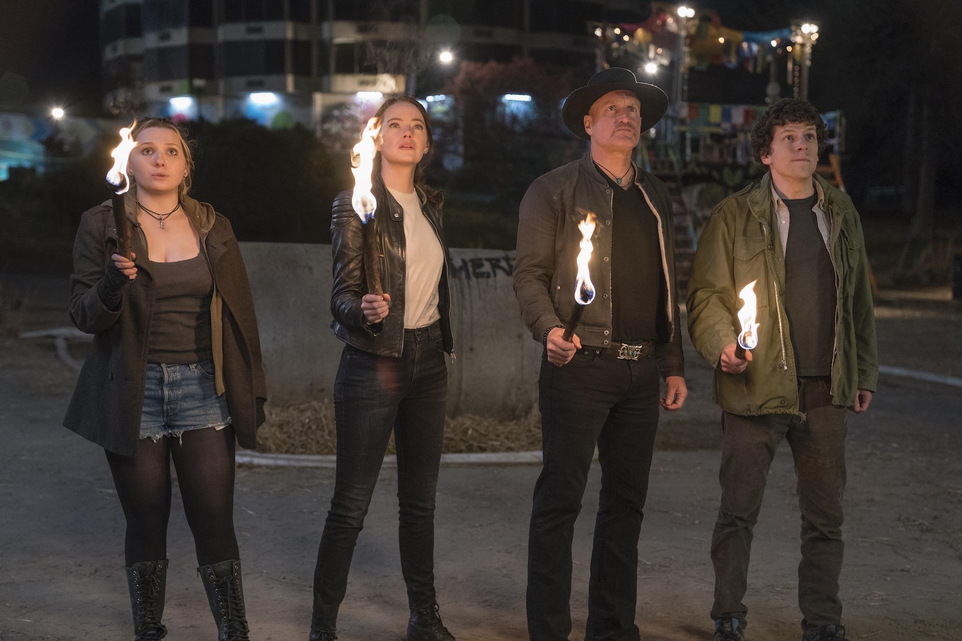 Little Rock (Abigail Breslin), Wichita (Emma Stone), Tallahassee (Woody Harrelson), and Columbus (Jesse Eisenberg) all bear torches.