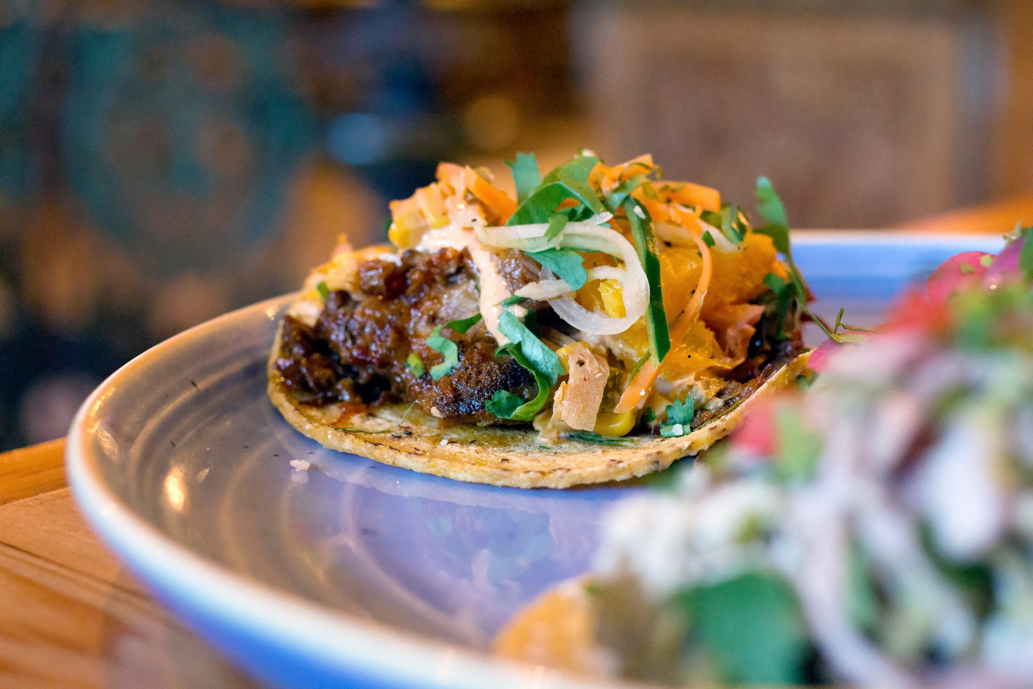 Tacos sit on a blue plate, with corn tortillas and meat and toppings piled high
