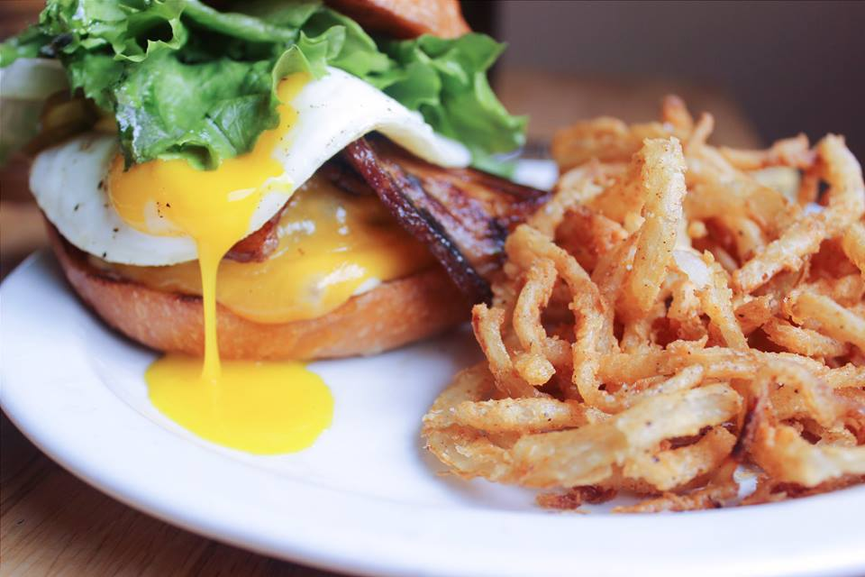 A picture of a burger with shoestring fries at Grain & Gristle