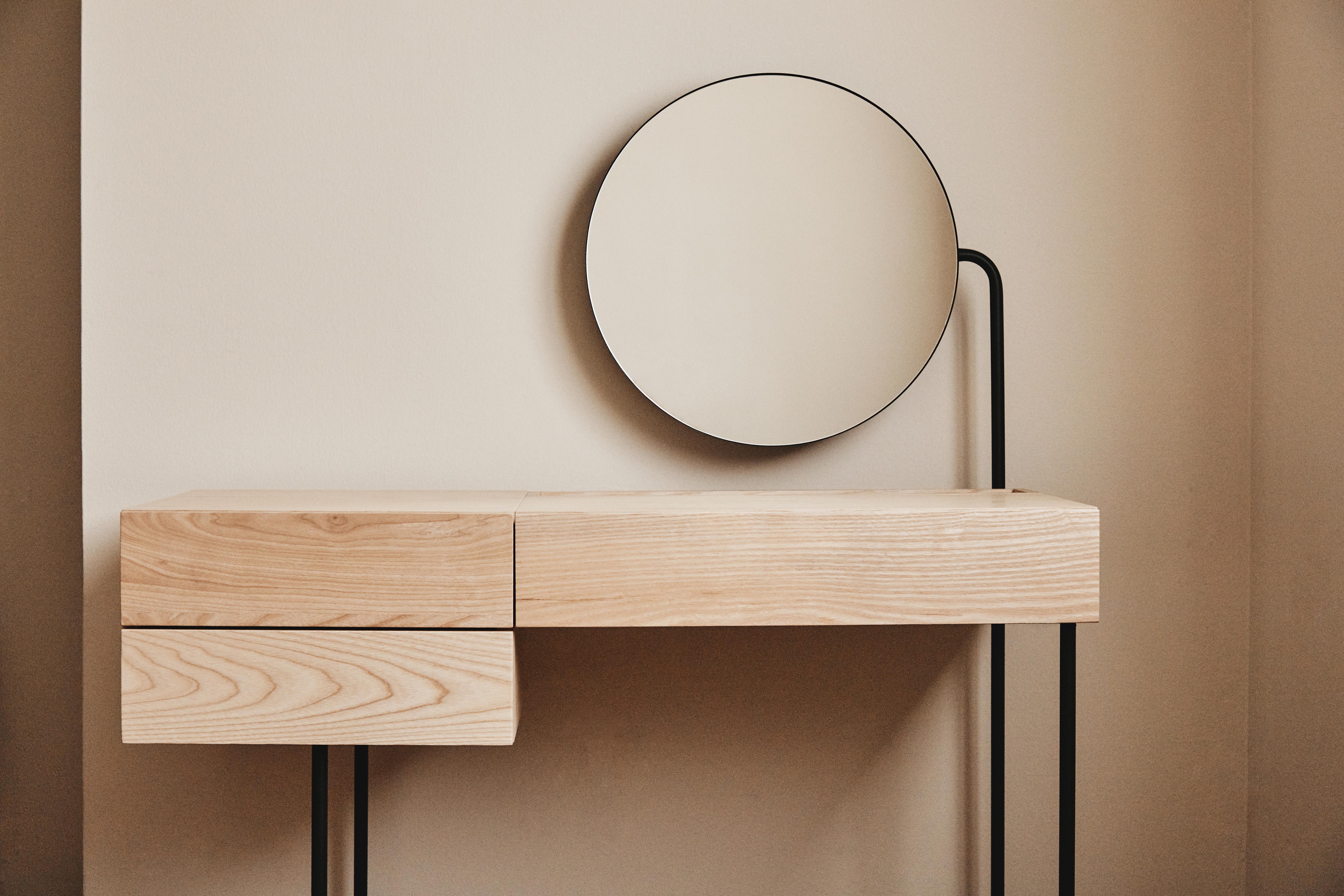 A natural wood desk with a circular mirror.