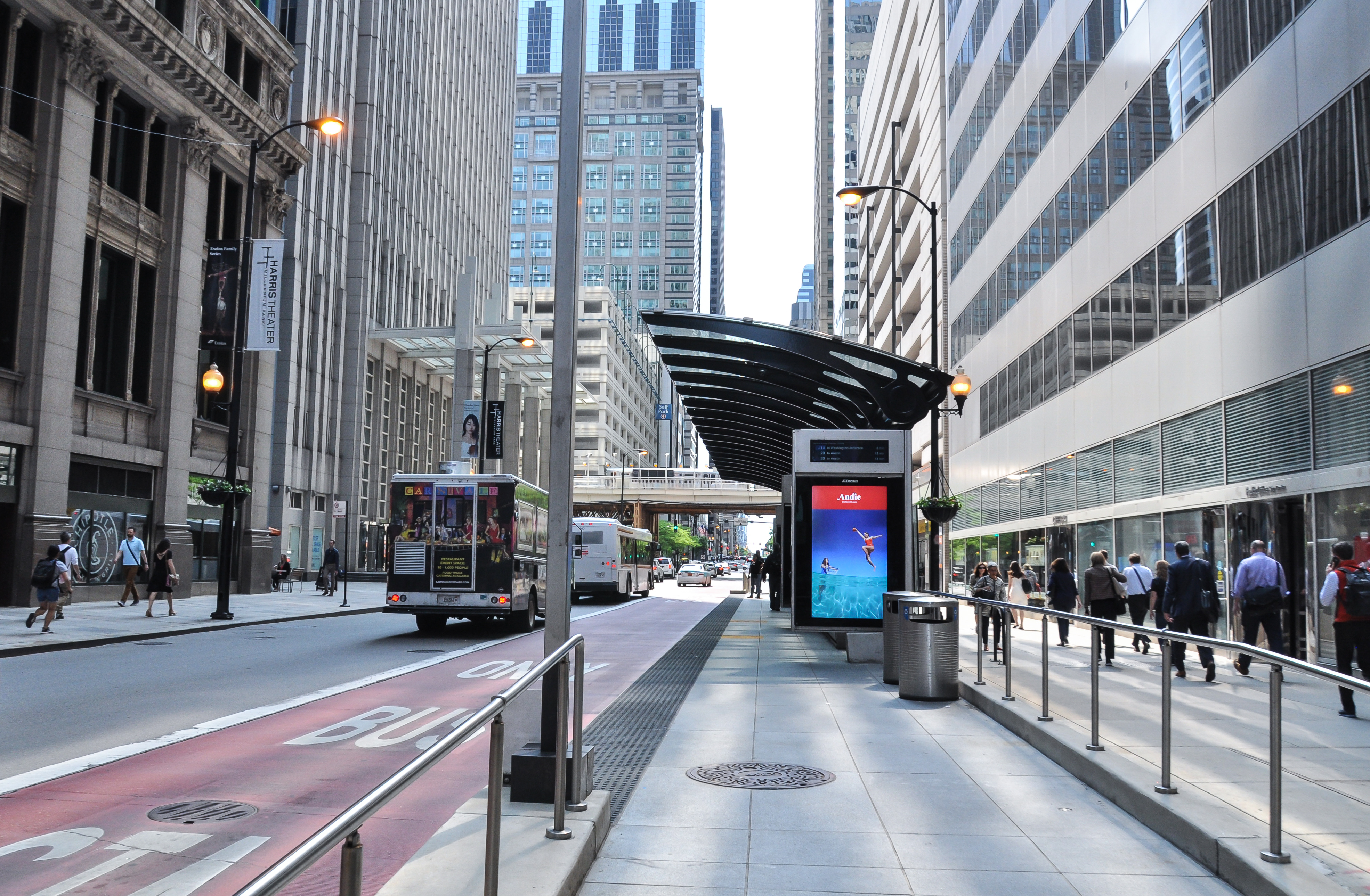 A red painted bus priority lane in downtown Chicago next to a bus shelter. There are tall buildings around the street and sidewalk.