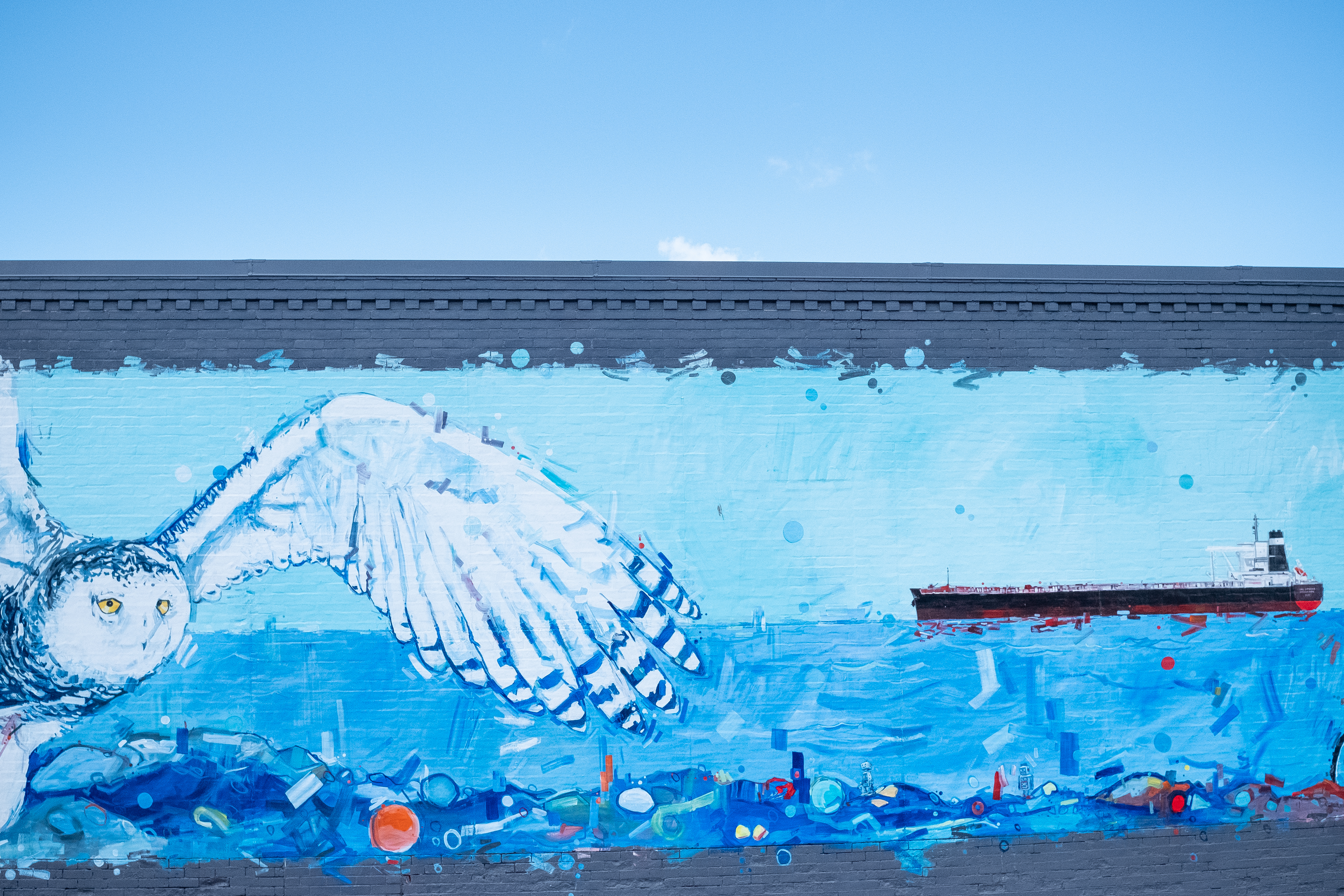 A blue-backed mural of Lake Superior with a ship and a snowy white owl in the foreground