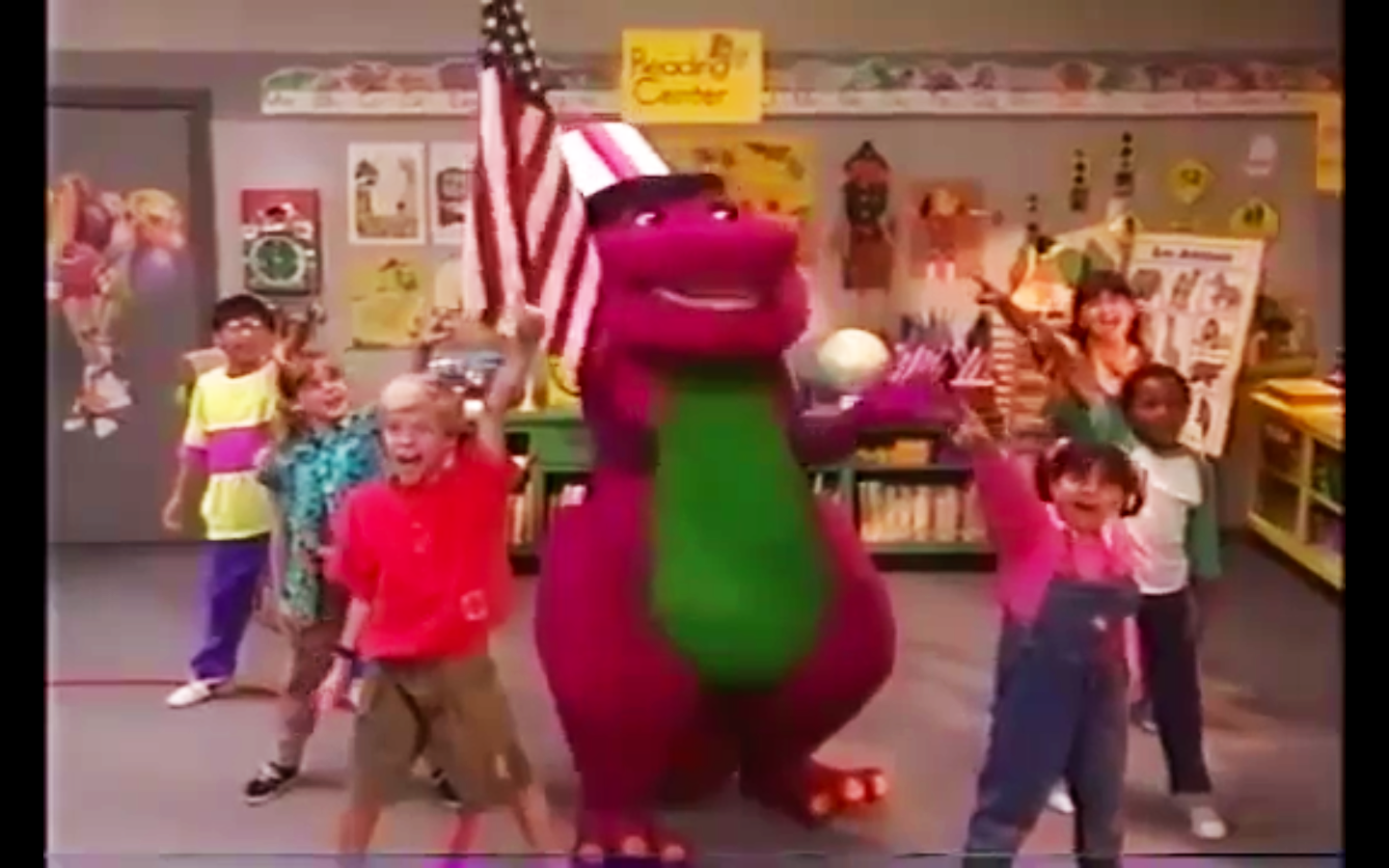 Barney the Dinosaur, wearing a patriotic hat and waving an American flag, leads a group of children in a song and dance.