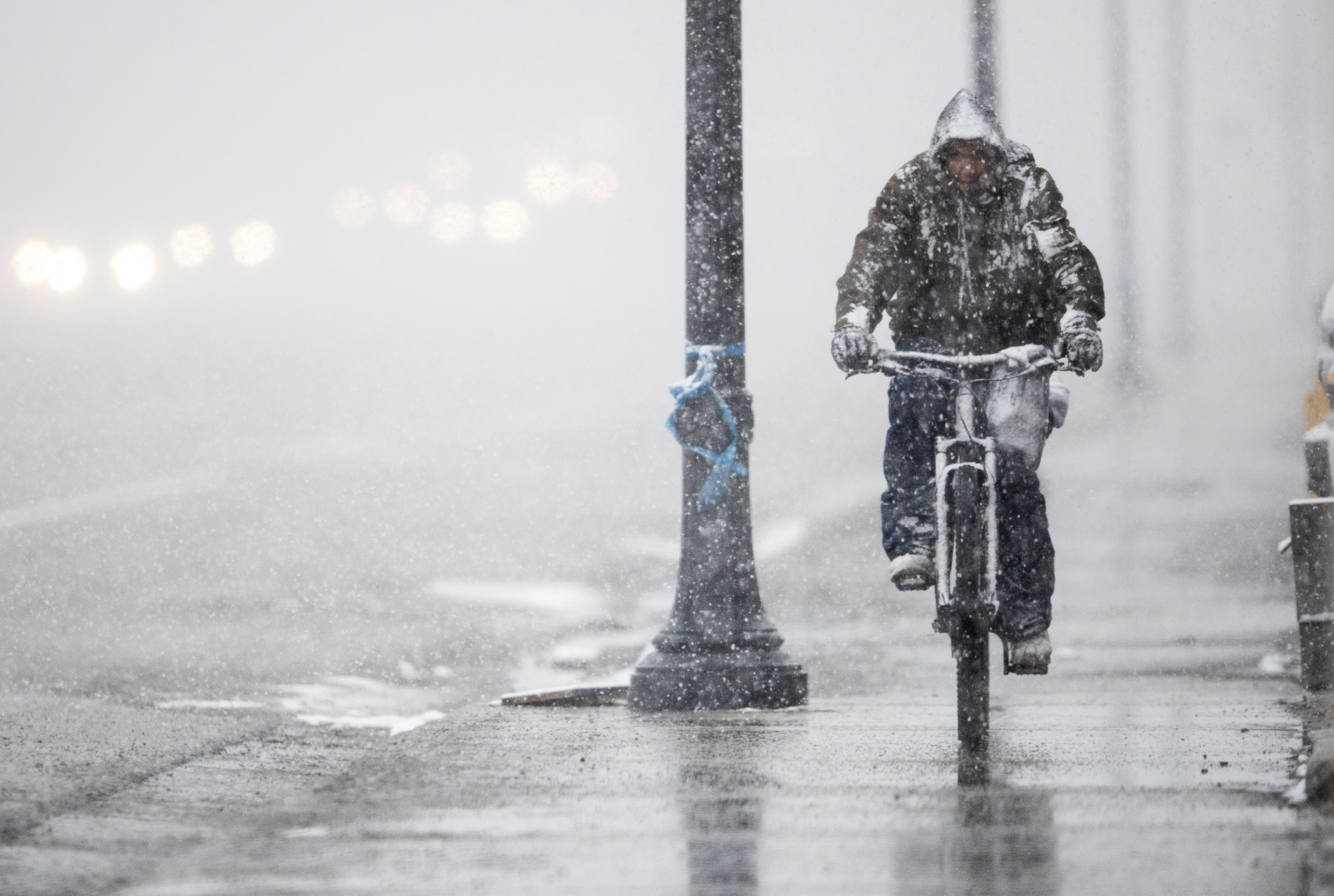 A man rides a bike in the snow in Murray on Sunday, Feb. 17, 2019.