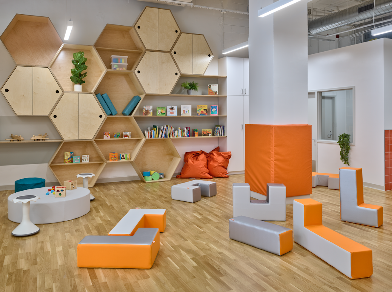 The interior of a daycare with orange bean baggies, cubbies filled with books, and plants.