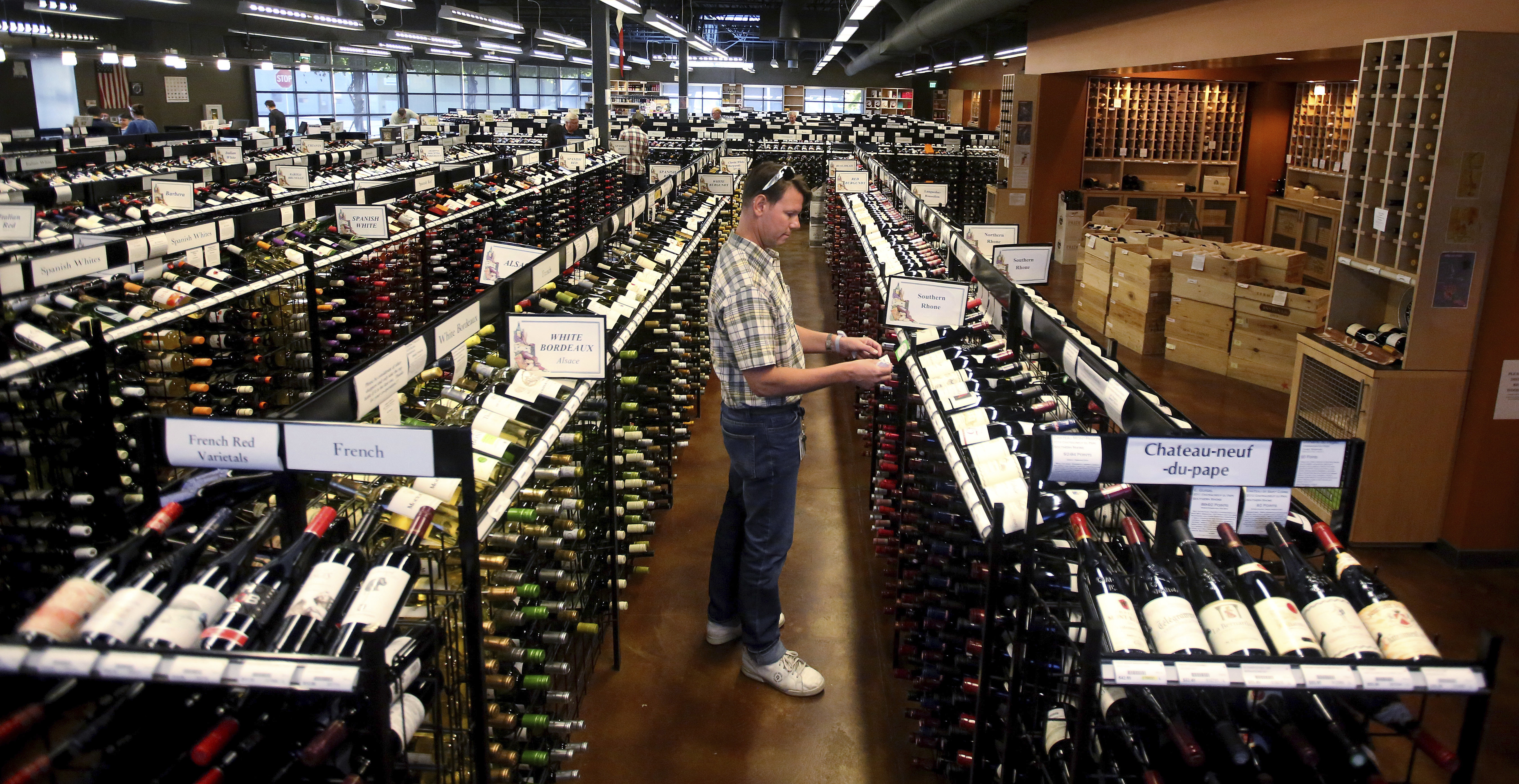 FILE - In this June 30, 2017, file photo, a worker at a state liquor store changes prices on wine, liquor and beer in Salt Lake City. Selection, beer and cold were among the words state-run liquor store customers used most in the Utah Department of Alcoho