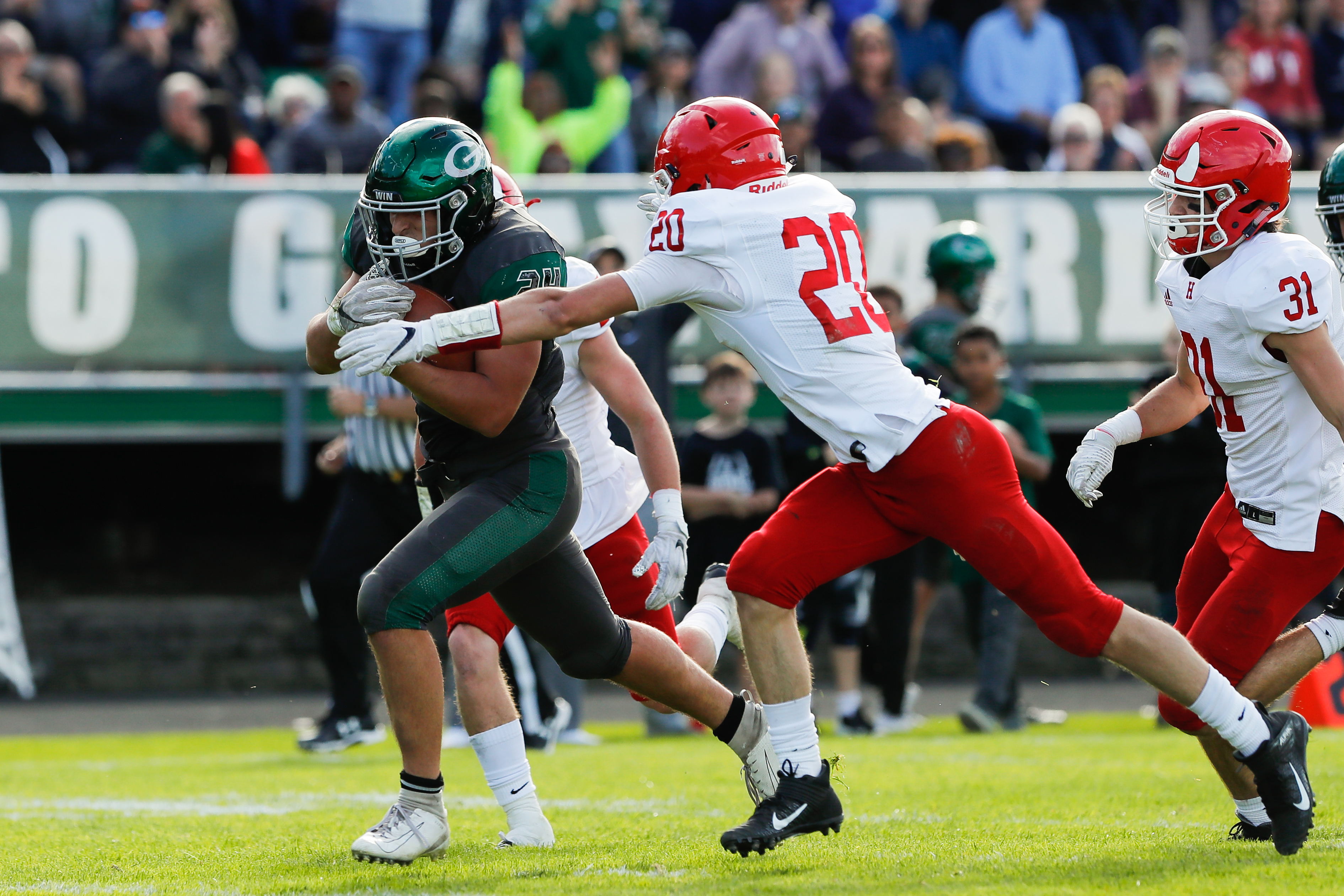 Glenbard West's Nic Seifert (24) runs against Hinsdale Central's defense.