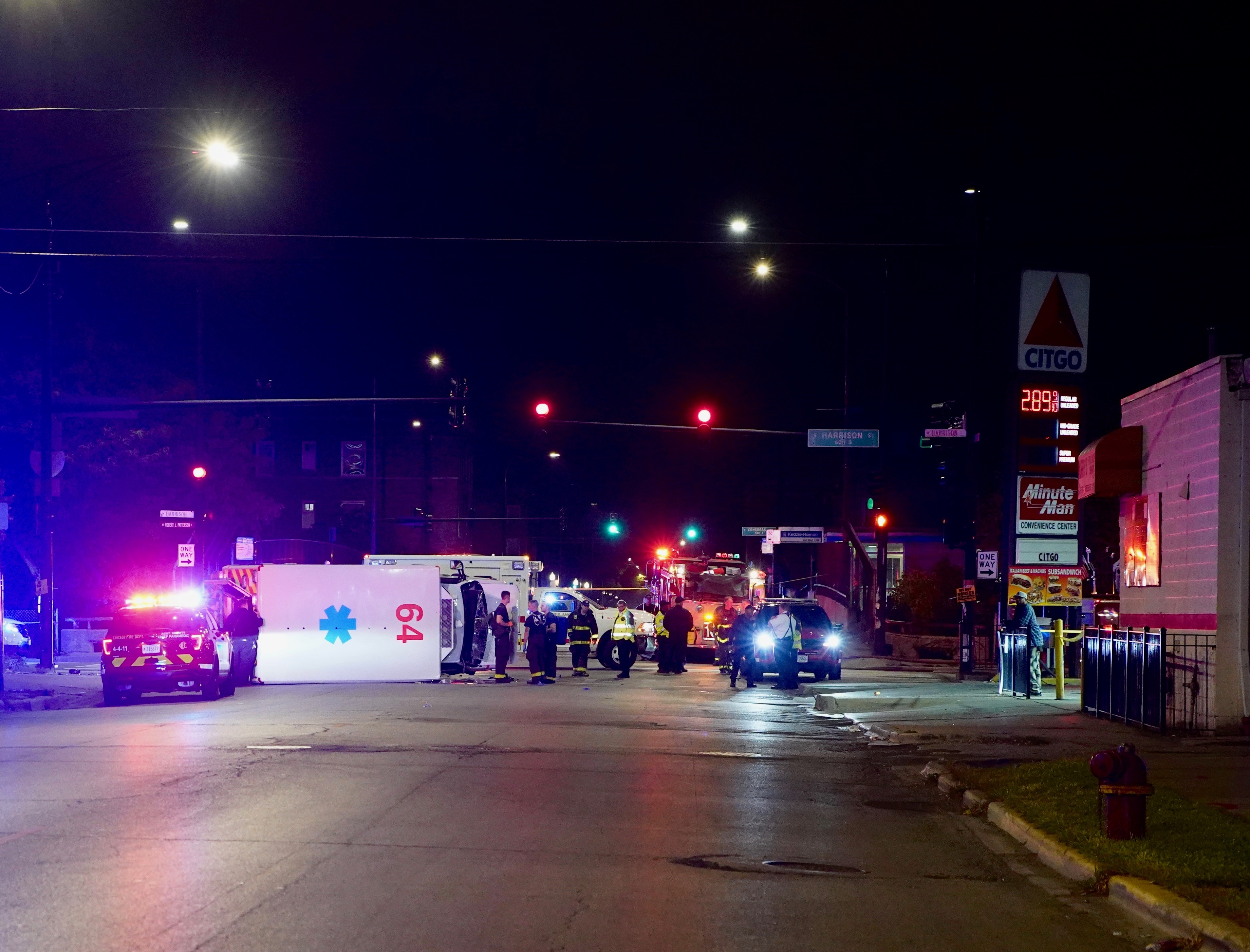 A Chicago Fire Department ambulance tipped over after being struck by a Chicago police cruiser while authorities were responding to a shooting Saturday in Homan Square.