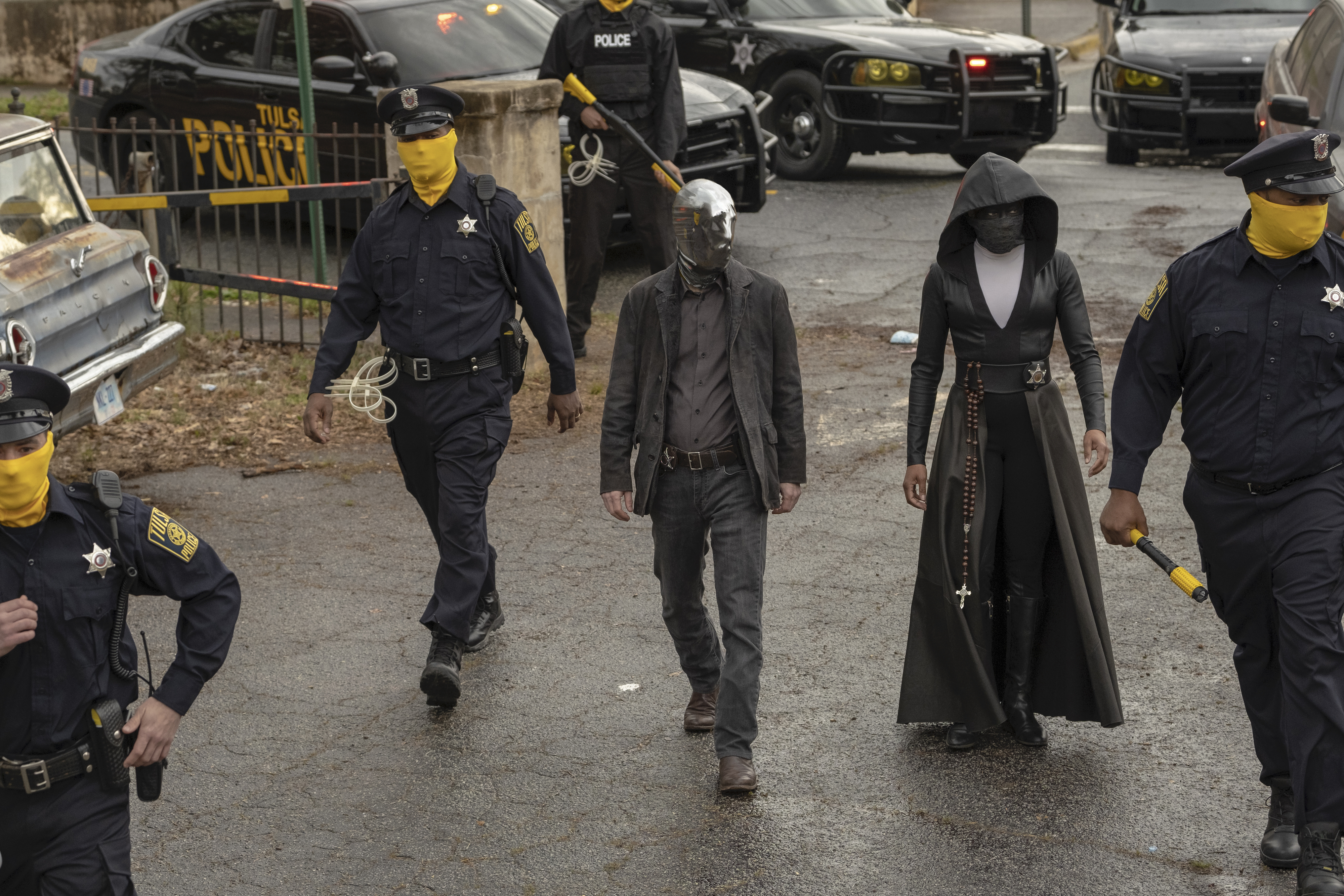 Vigilantes Looking Glass (Tim Blake Nelson) and Sister Night (Regina King) walk into a crime scene flanked by masked police officers.
