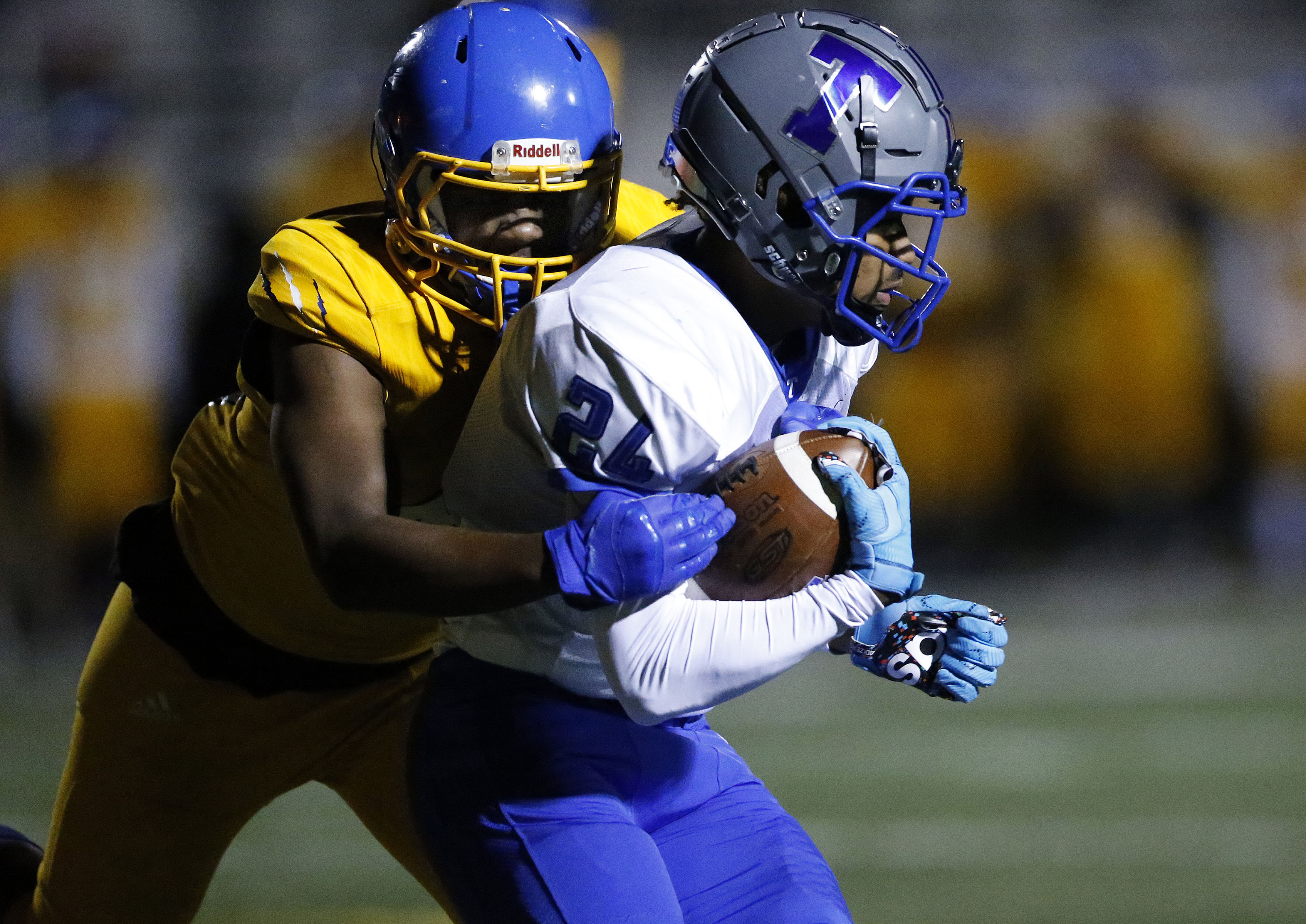 Taft's David Dunbar (24) is brought down by Simeon's Latrell Scott (44).