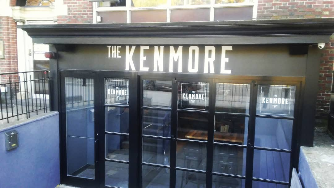 """The window-filled black exterior of a basement level restaurant. White capital letters read """"The Kenmore."""""""