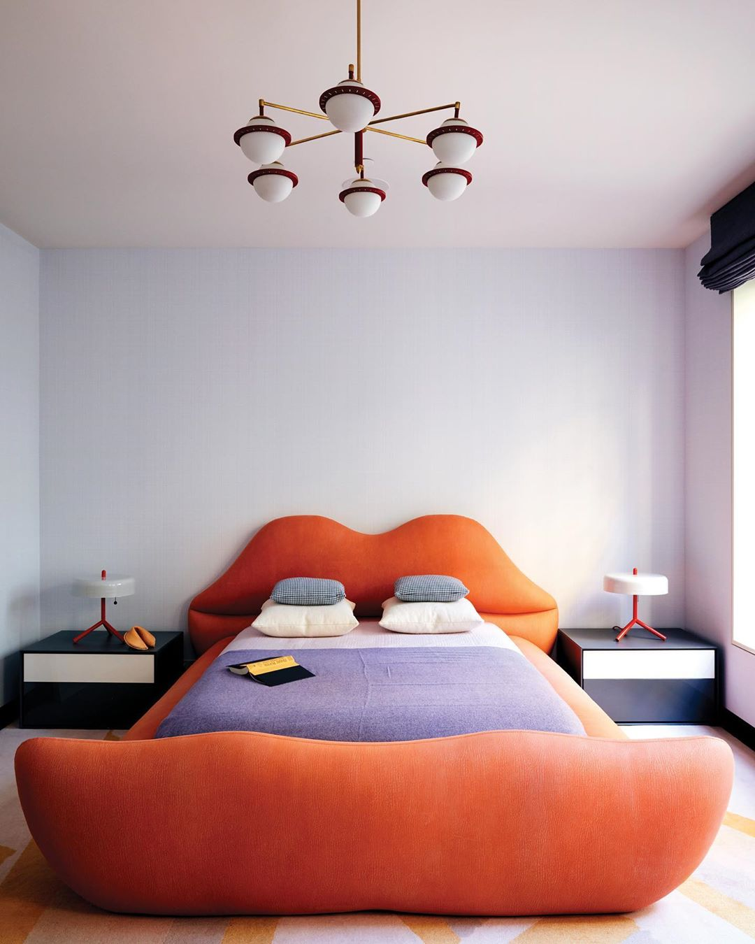 A large red bed holds a mattress covered in purple bedsheets with four pillows. There are two side table lamps, one on each sidle of the bed. A seven-bulb white and brass light fixture hangs from above.