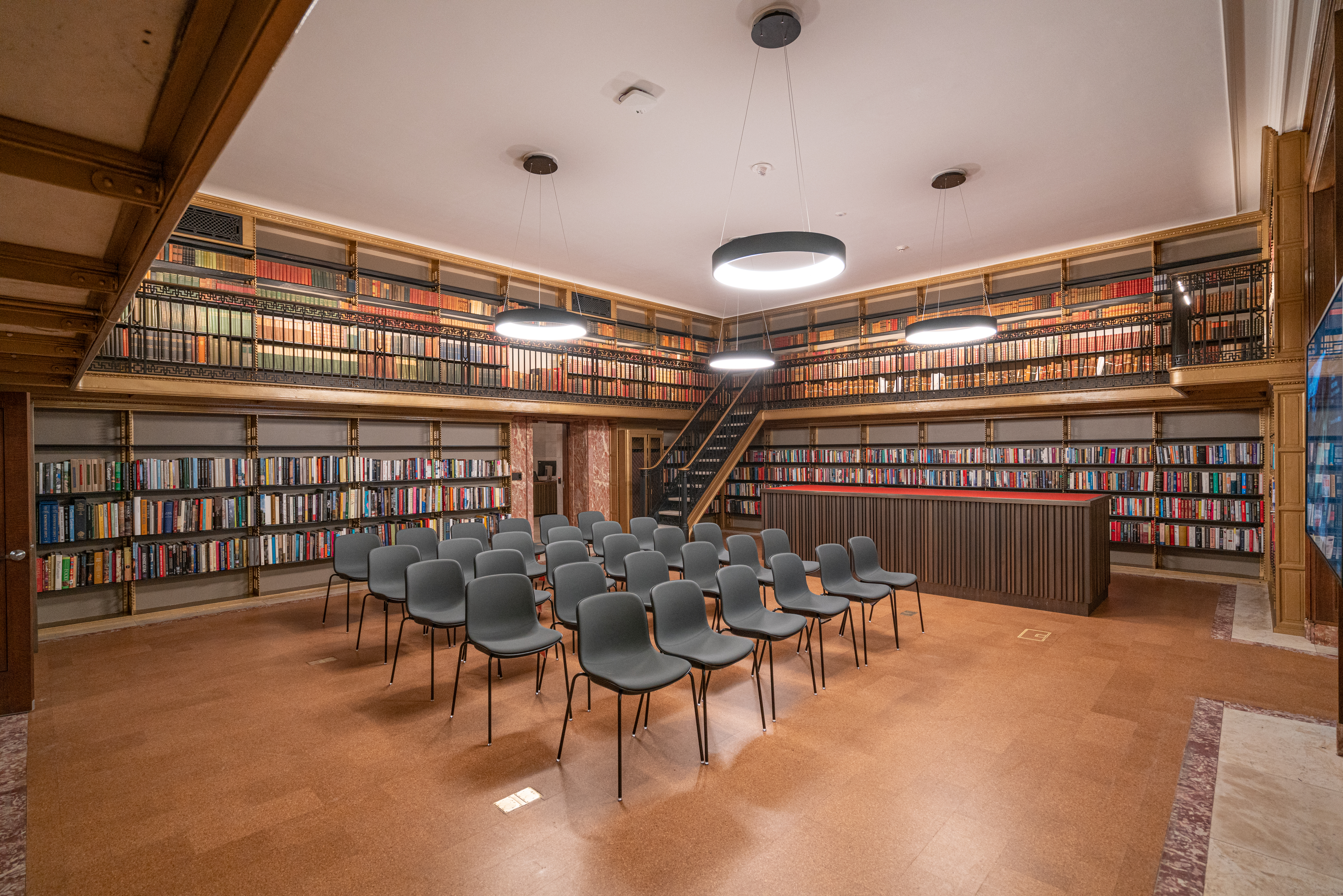 A library room with several chairs, wooden floors, and stacks filled with books.