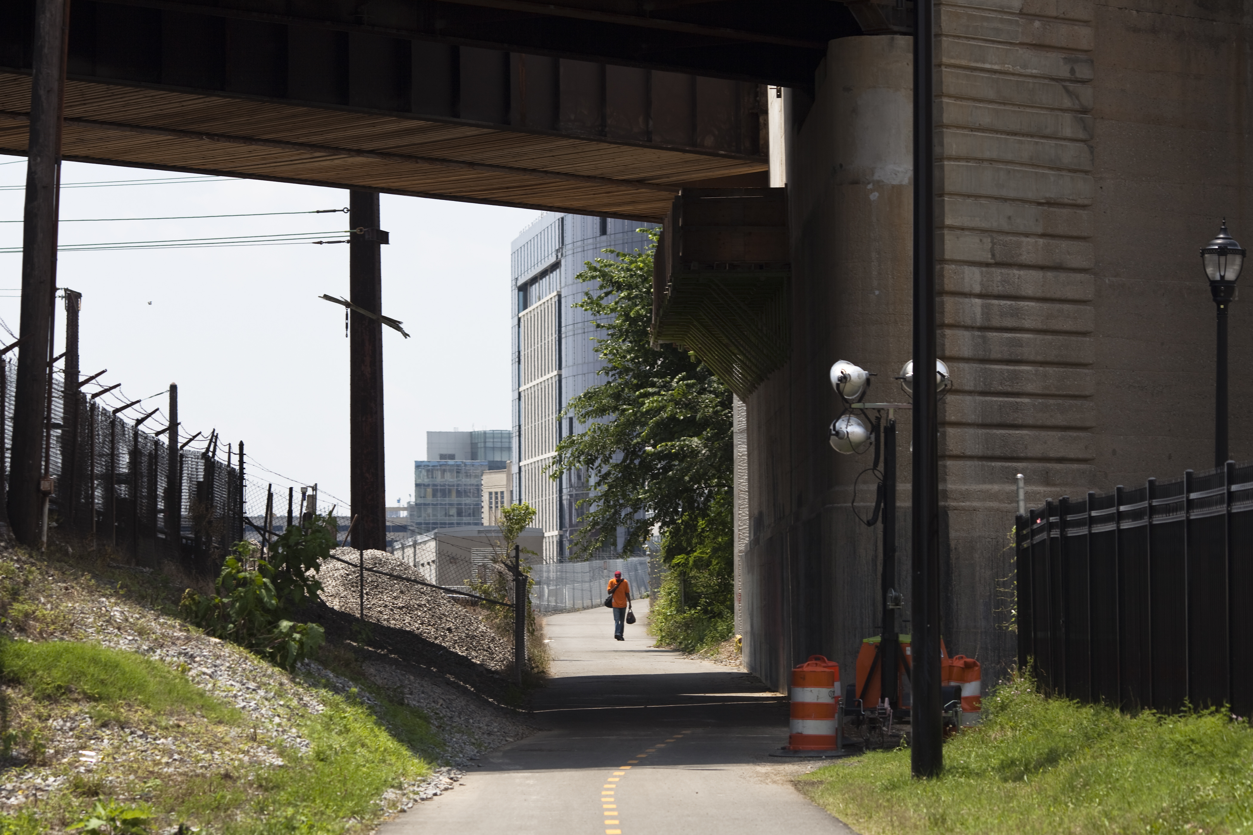 A two-way multiuse trail runs under an overpass. A man is seen walking on the trail in the distance.
