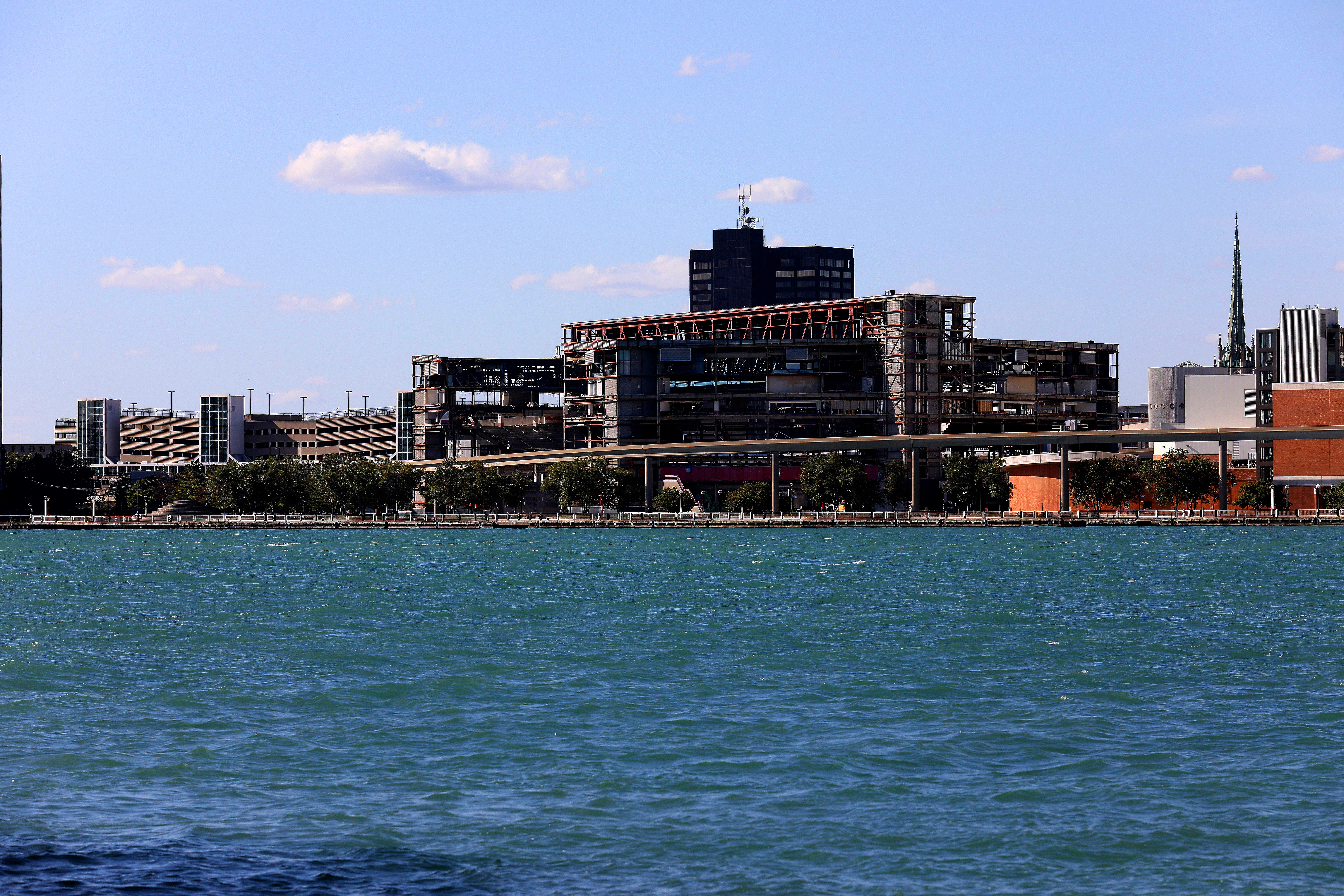 View across the Detroit River of a partially deconstructed buildings. All that's left is the steel support structure.