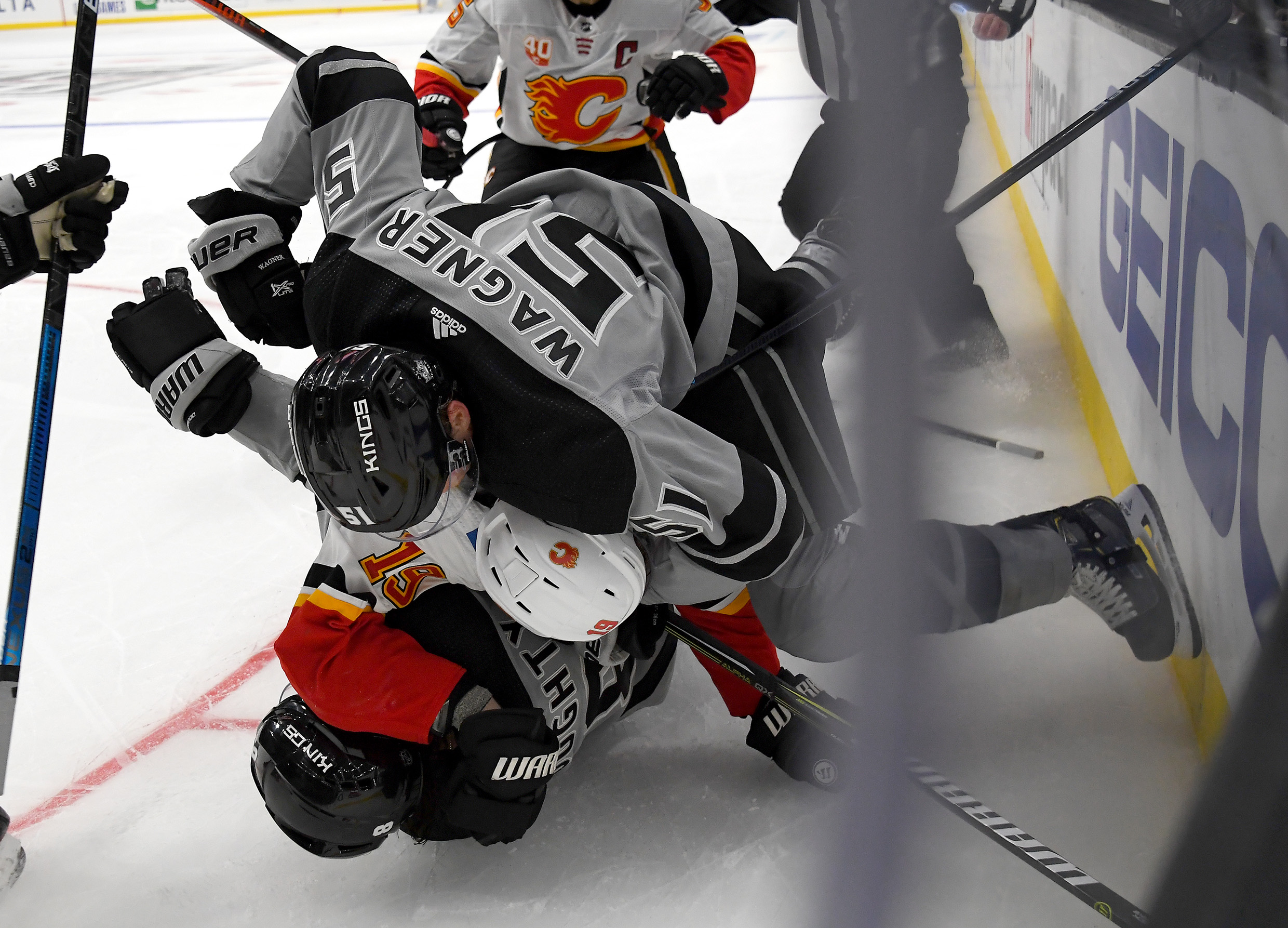 Los Angeles Kings defenseman Drew Doughty (8) is taken down by Calgary Flames center Tobias Rieder (16) as Los Angeles left wing Austin Wagner (51) jumps on the pile in the third period at Staples Center
