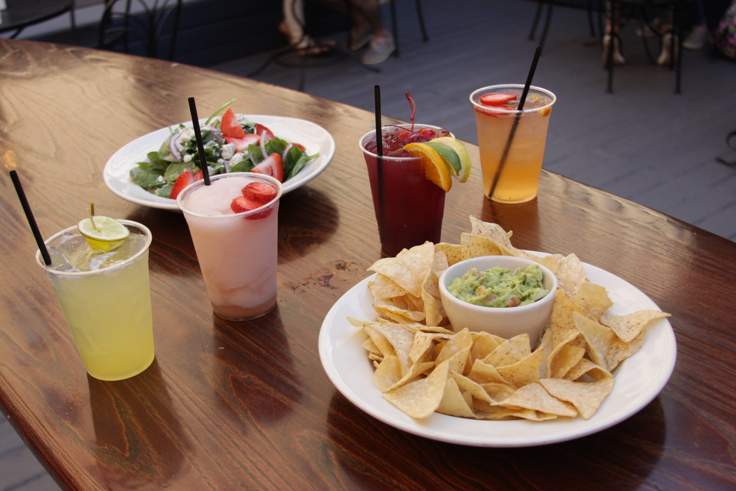 A plate of chips with guacamole sits on a table with four drinks and a salad