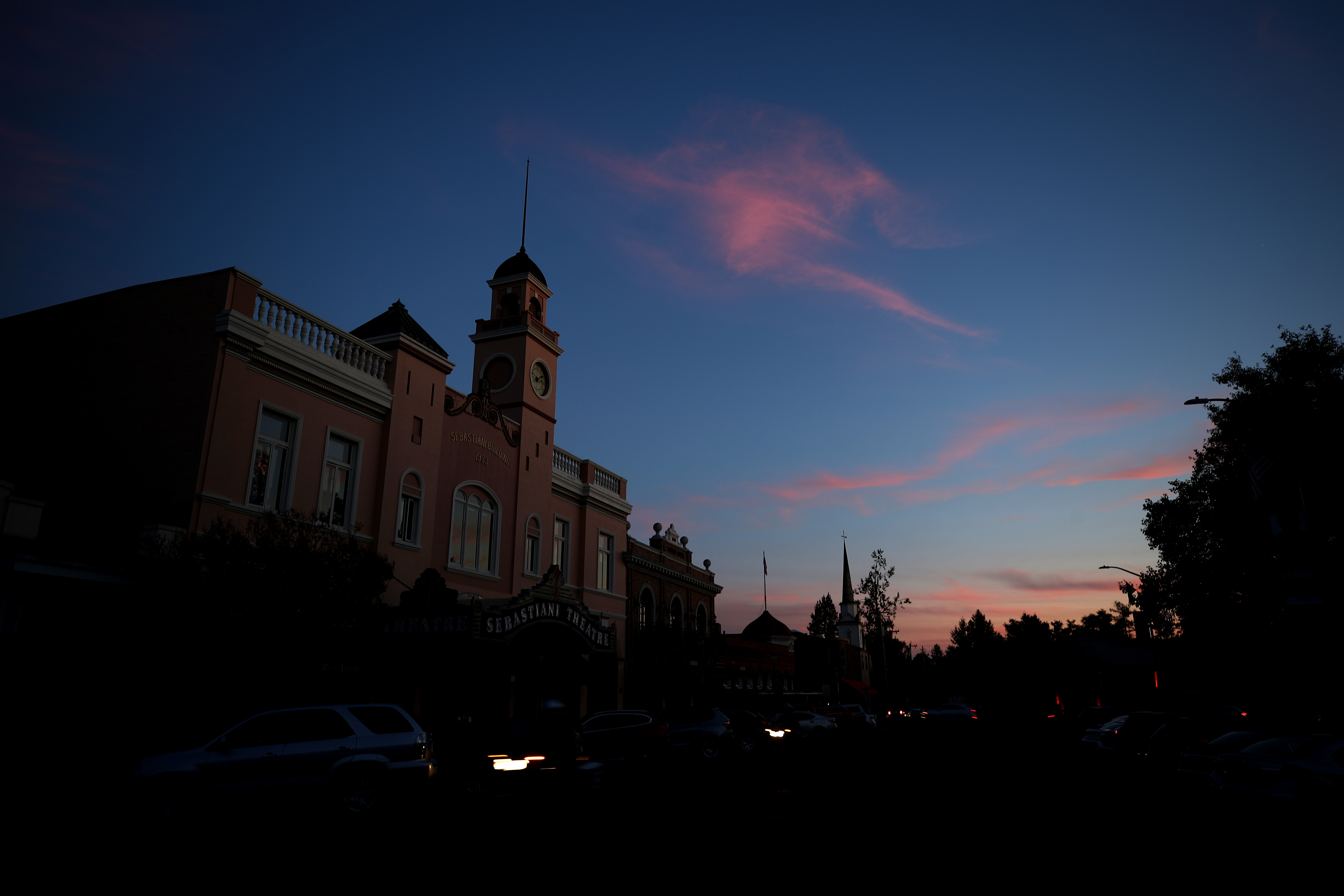 A white building with a steepled tower, surrounded by dark trees, with a sunset in the sky above.