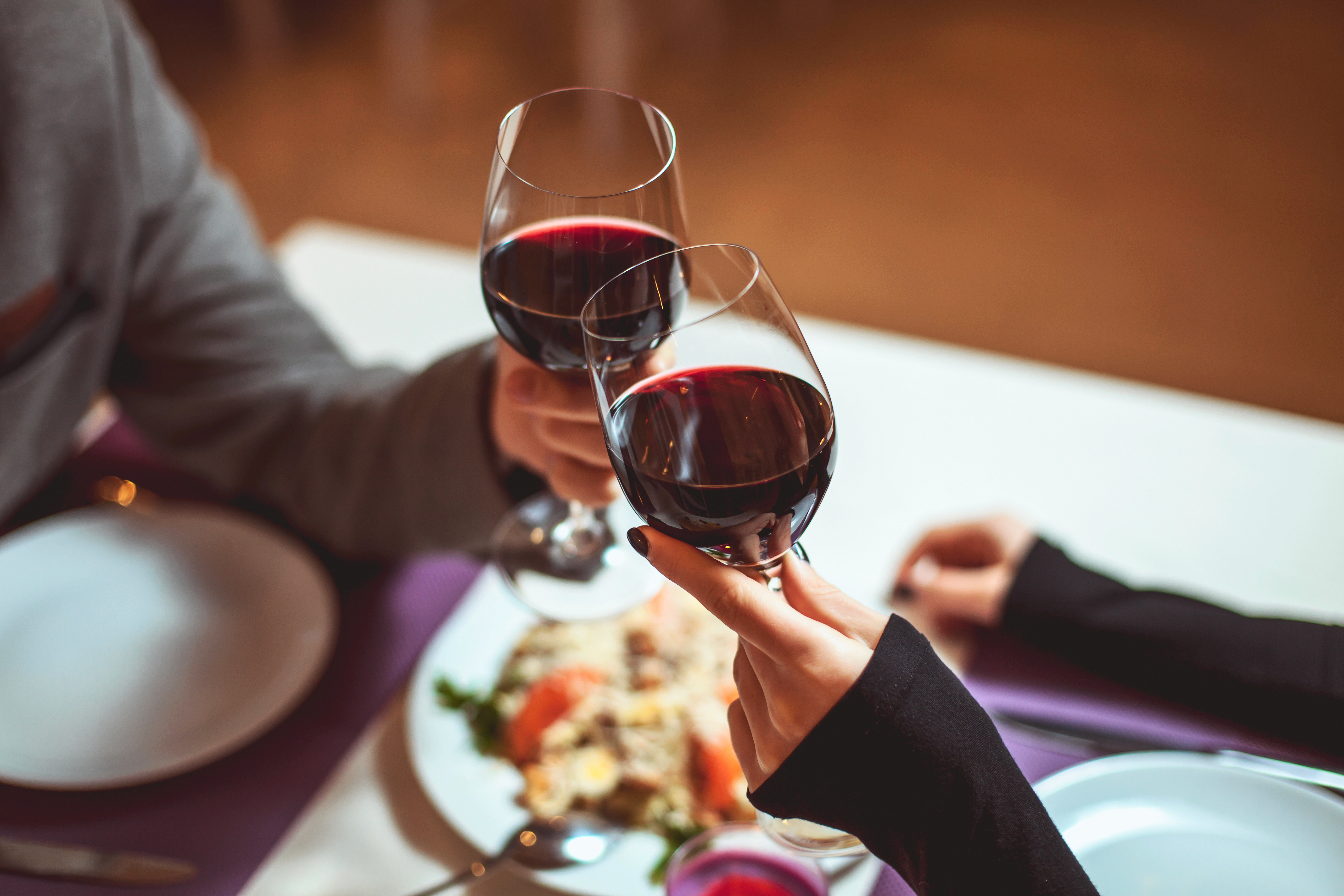 Two people share two glasses of red wine over a plate of food at a restaurant.