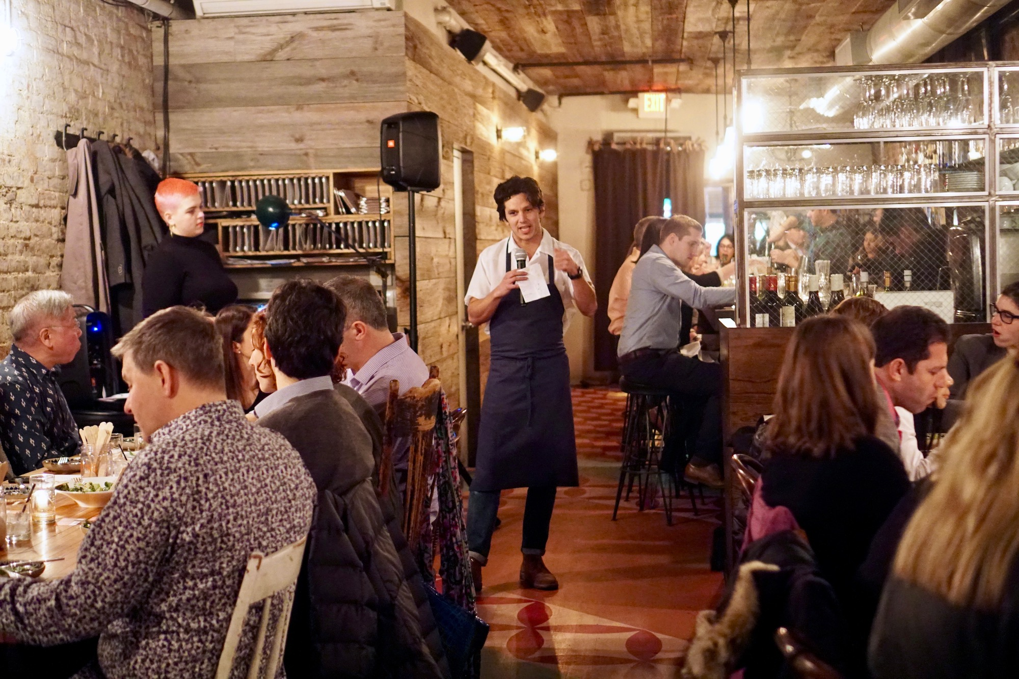A chef talks to a room of diners at a private dinner, while holding a microphone.