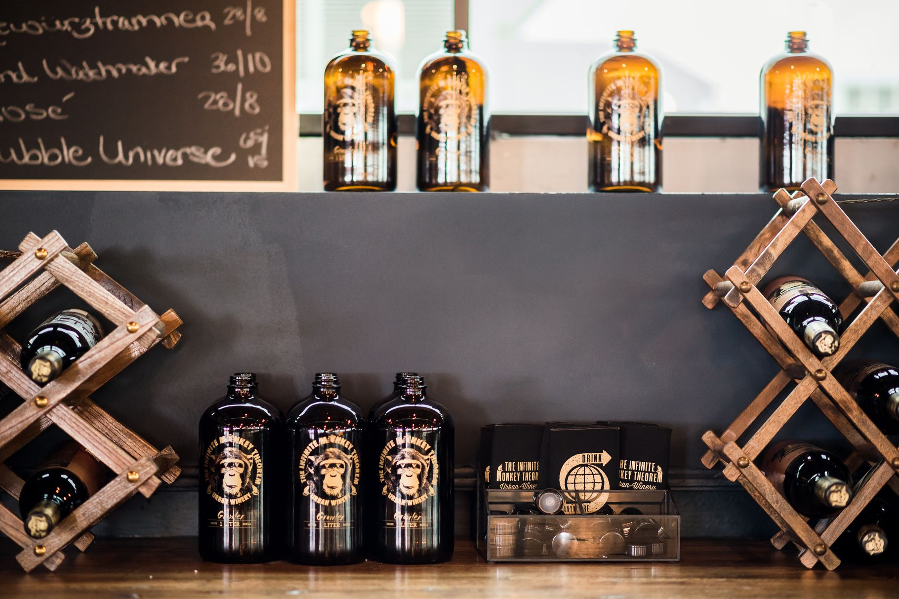 A photo of several wine growlers on a countertop at Infinite Monkey Theorem with a menu board partially visible behind them.