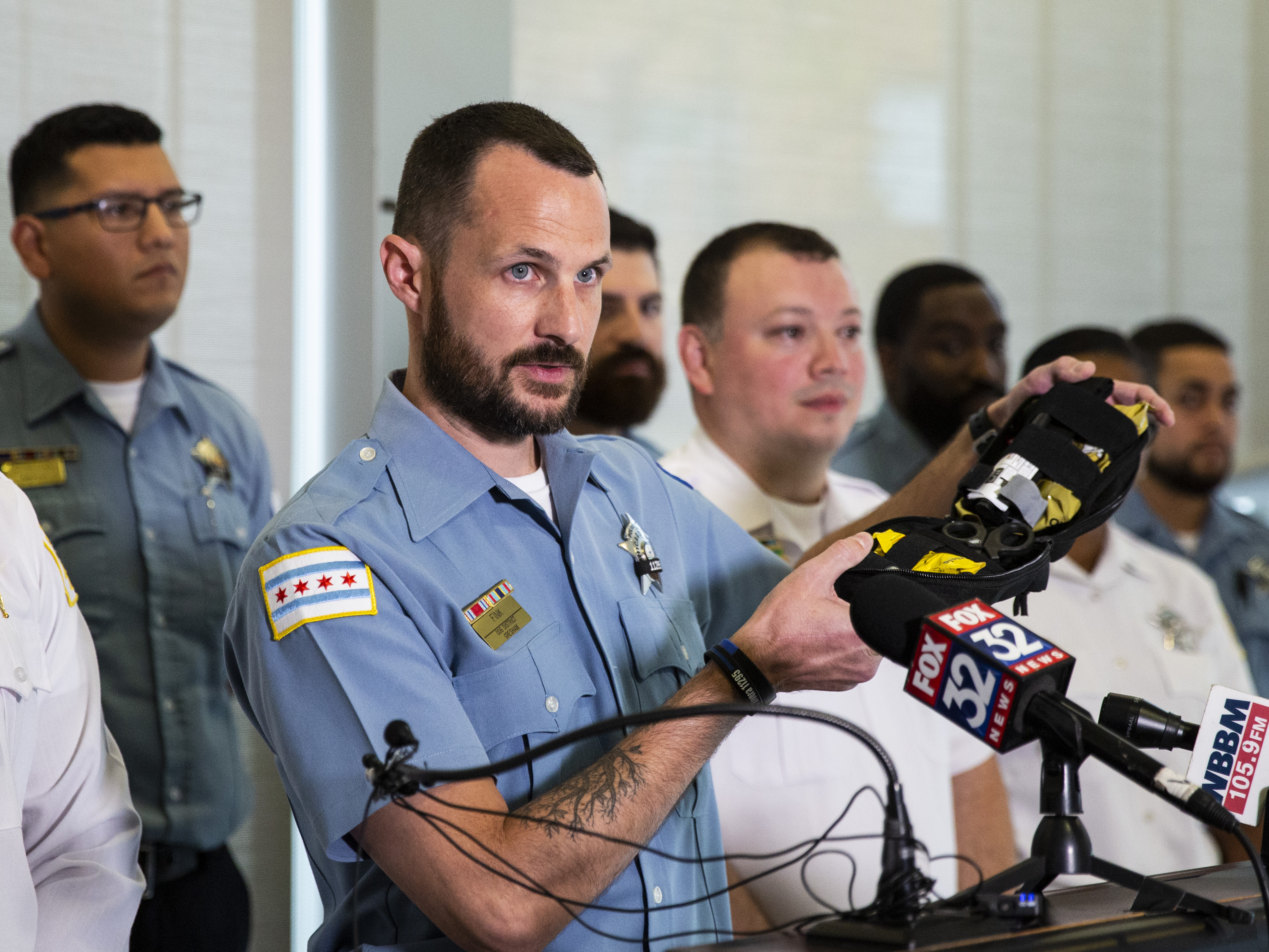 Chicago Police Officer Christopher Fink holds up equipment he used while he and other first responders saved a 14-year-old boy who was shot in the chest earlier this month during a press conference at the Gresham station, Monday morning, Oct. 21, 2019.